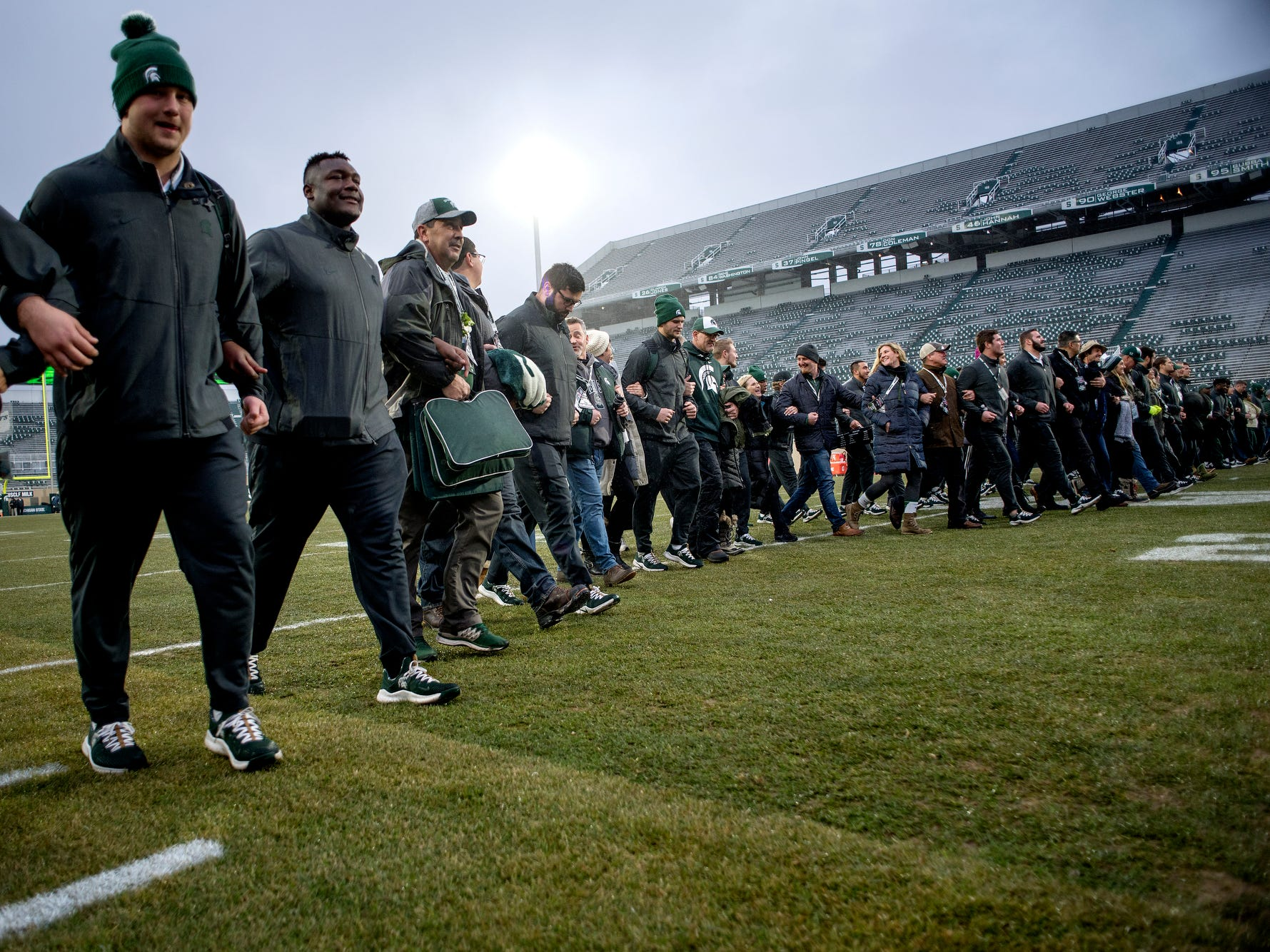 Michigan State players and the seniors' family members walk across the field before the game against Rutgers on Saturday, Nov. 24, 2018, at Spartan Stadium in East Lansing.