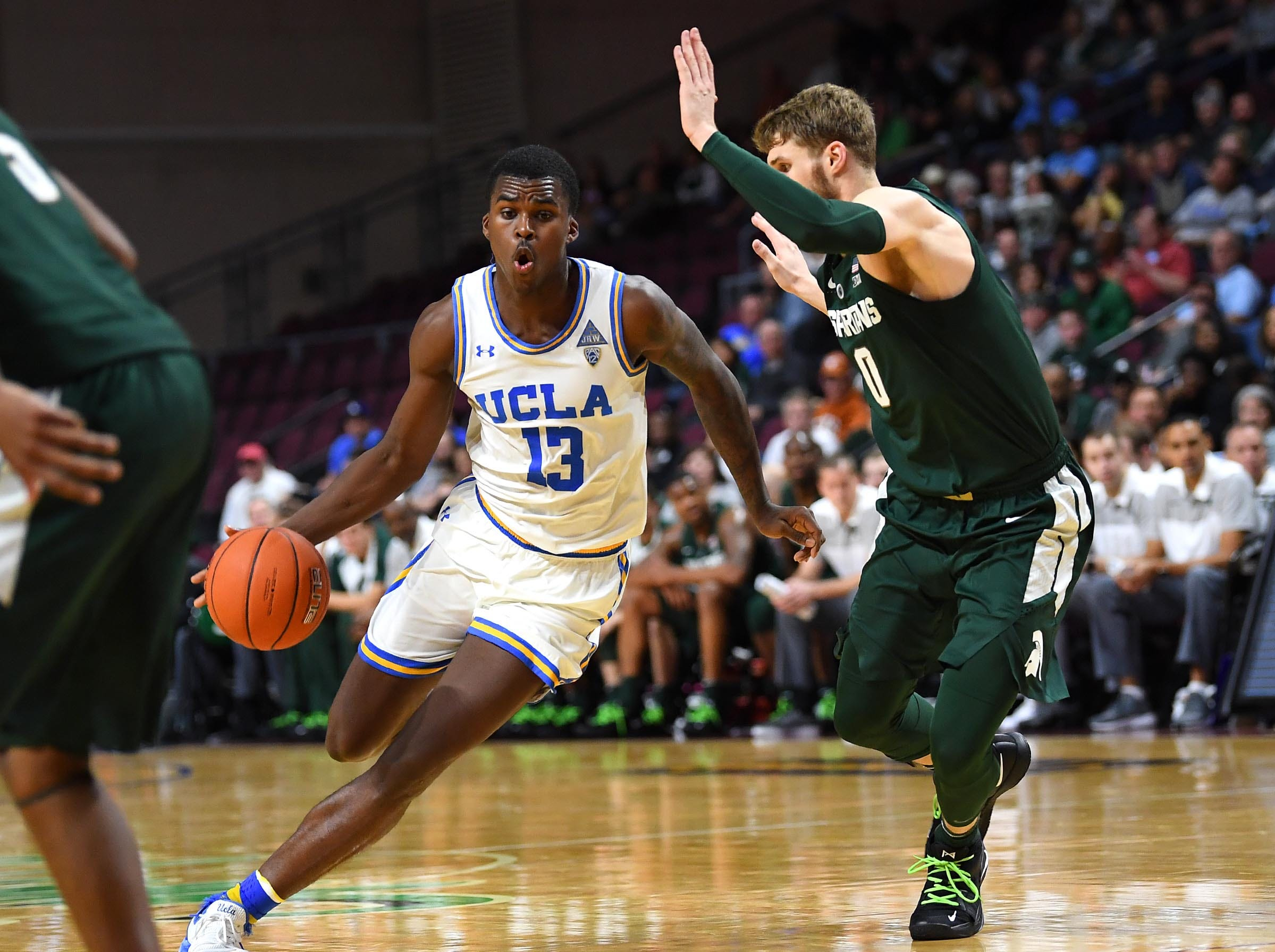 Nov 22, 2018; Las Vegas, NV, USA; UCLA Bruins guard Kris Wilkes (13) dribbles against Michigan State Spartans forward Kyle Ahrens (0) during the second half at Orleans Arena. Mandatory Credit: Stephen R. Sylvanie-USA TODAY Sports