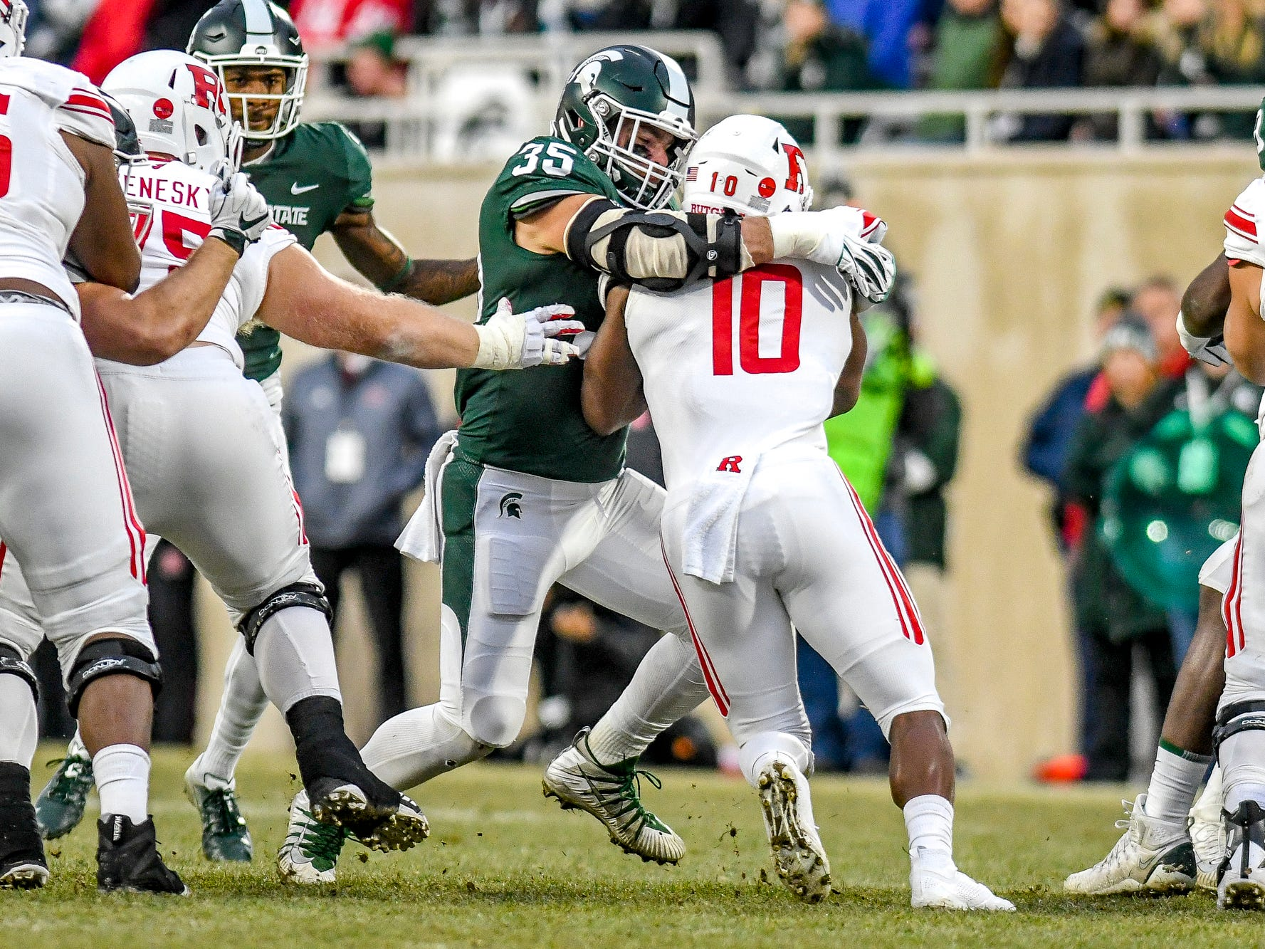 Michigan State's Joe Bachie, left, tackles Rutgers Isaih Pacheco during the first quarter on Saturday, Nov. 24, 2018, at Spartan Stadium in East Lansing.