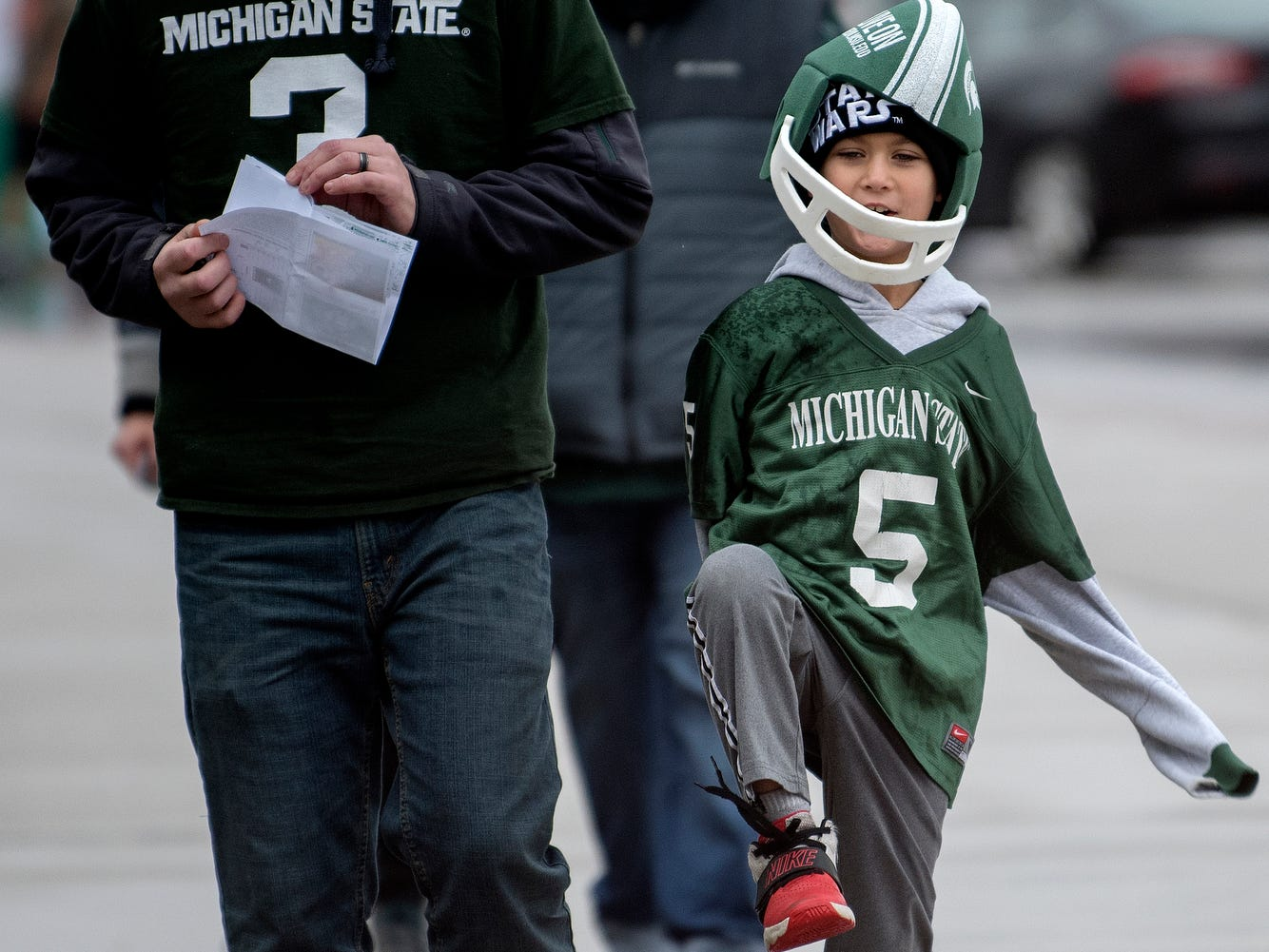 Spartans fan Greyson Rountree, 7, right, and his father Josh make their way to the entry game before Michigan State's game against Rutgers on Saturday, Nov. 24, 2018, outside Spartan Stadium in East Lansing.