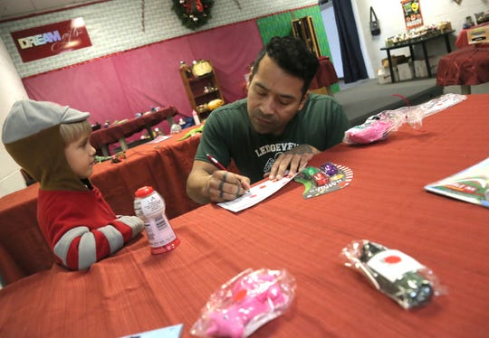 Aurelio Diaz helps Elijah Rader, 4; pick out gifts for his family at Tiny Tim Shoppe on Saturday.