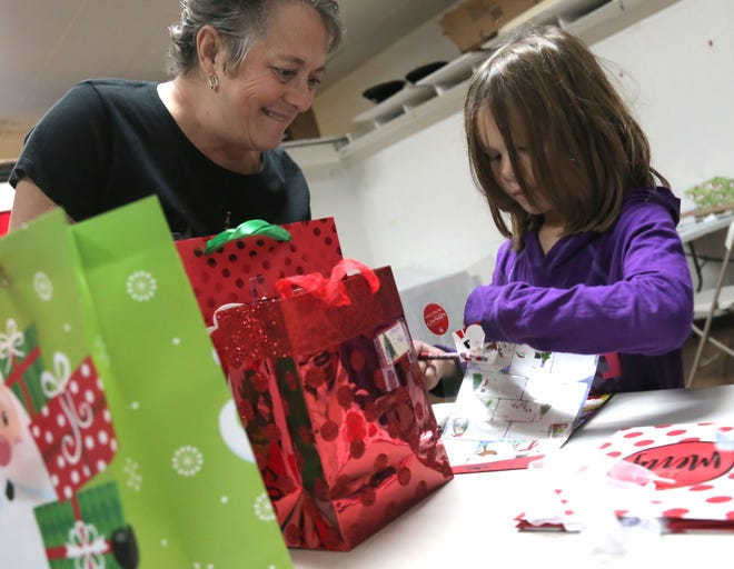 Annie Thart helps Abbie Pairan, 6, pack her gifts at Tiny Tim Shoppe on Saturday.