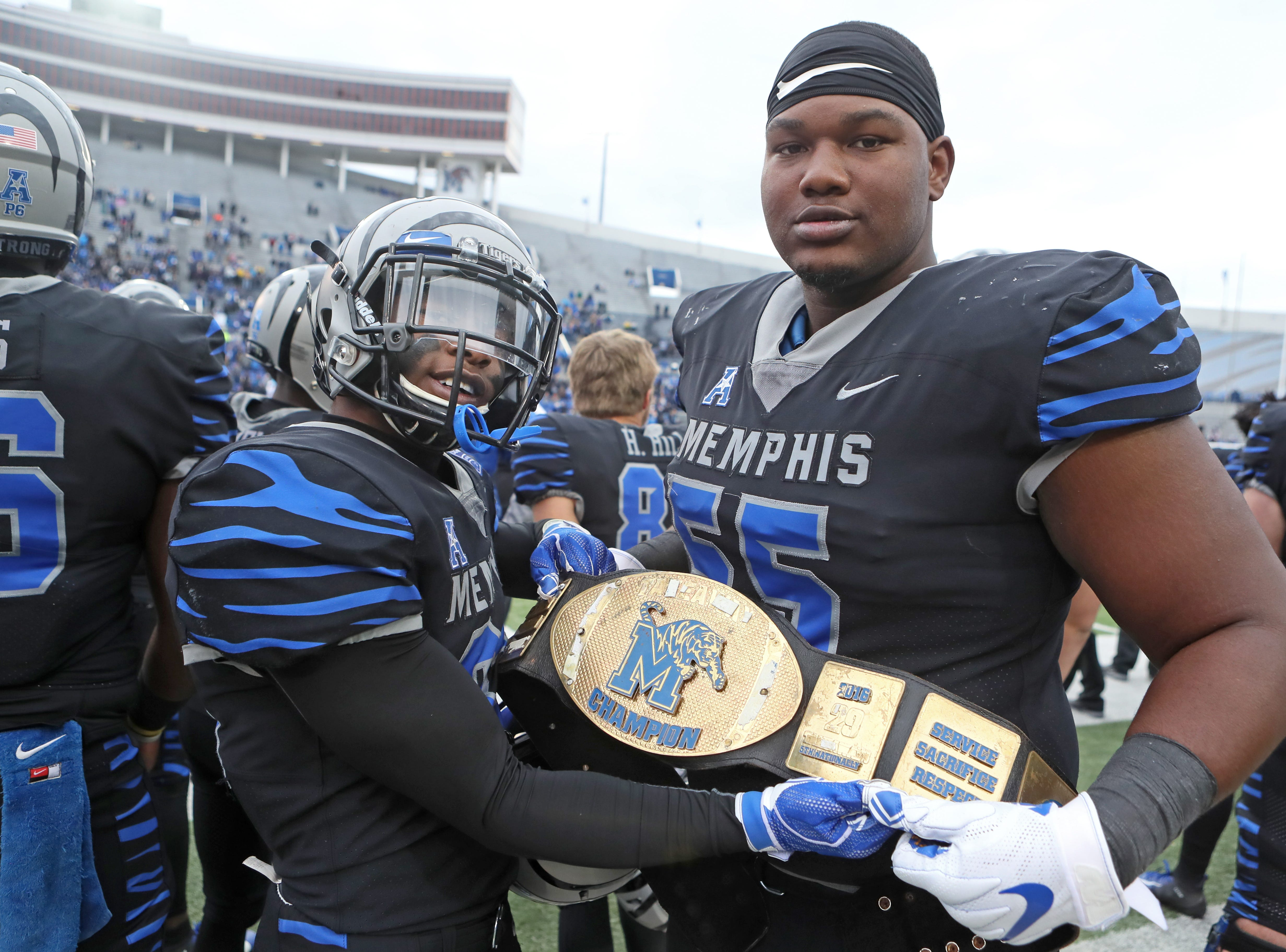 Memphis players Tamaurice Smith, left, and Mikhail Hill celebrate their title against the Houston Cougars as the Tigers win the AAC West 52-31 at the Liberty Bowl on Friday, Nov. 23, 2018.