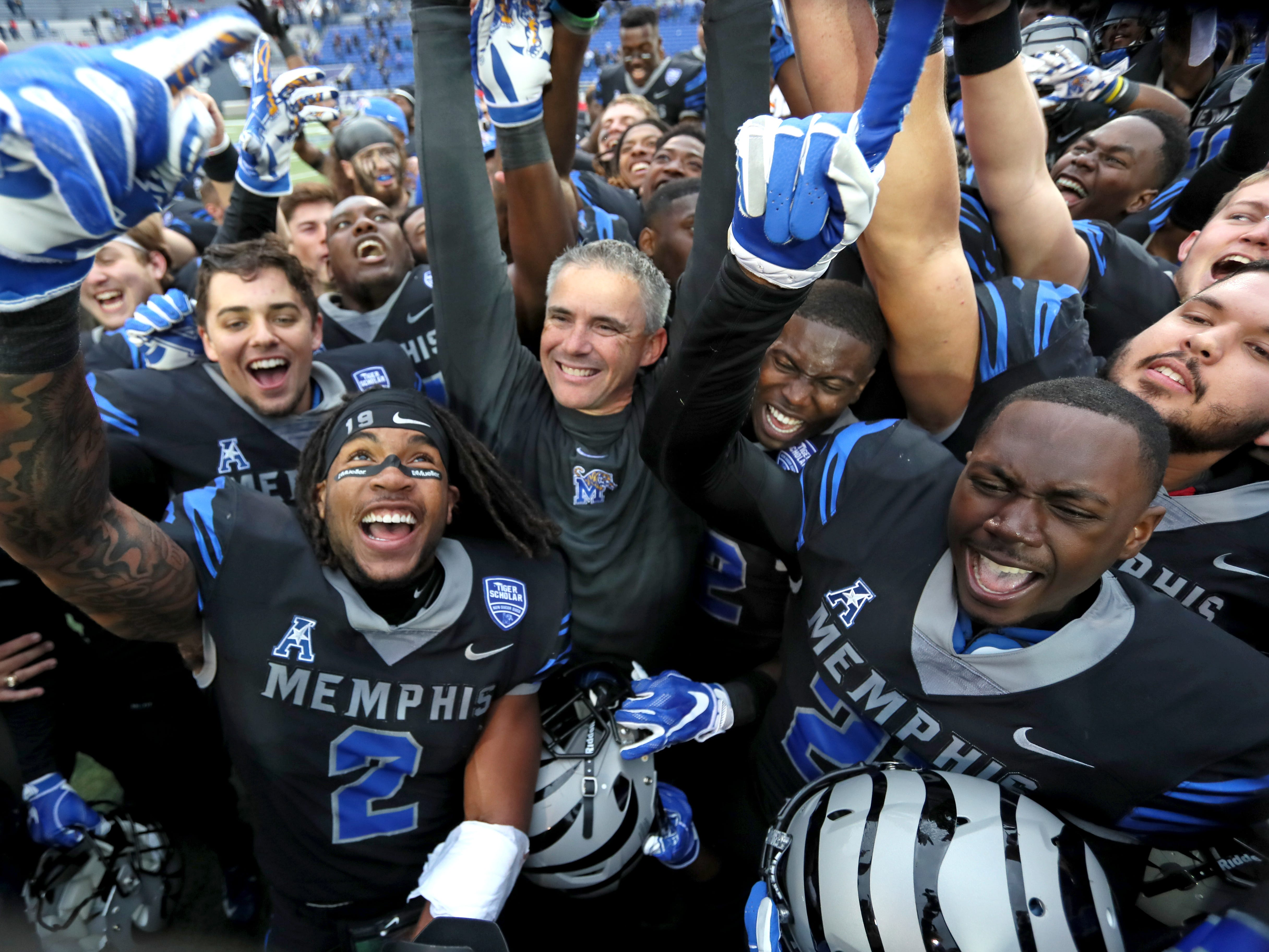 Memphis Head Coach Mike Norvell celebrates with his team as they defeat the Houston Cougars to win the AAC West title 52-31 at the Liberty Bowl on Friday, Nov. 23, 2018.
