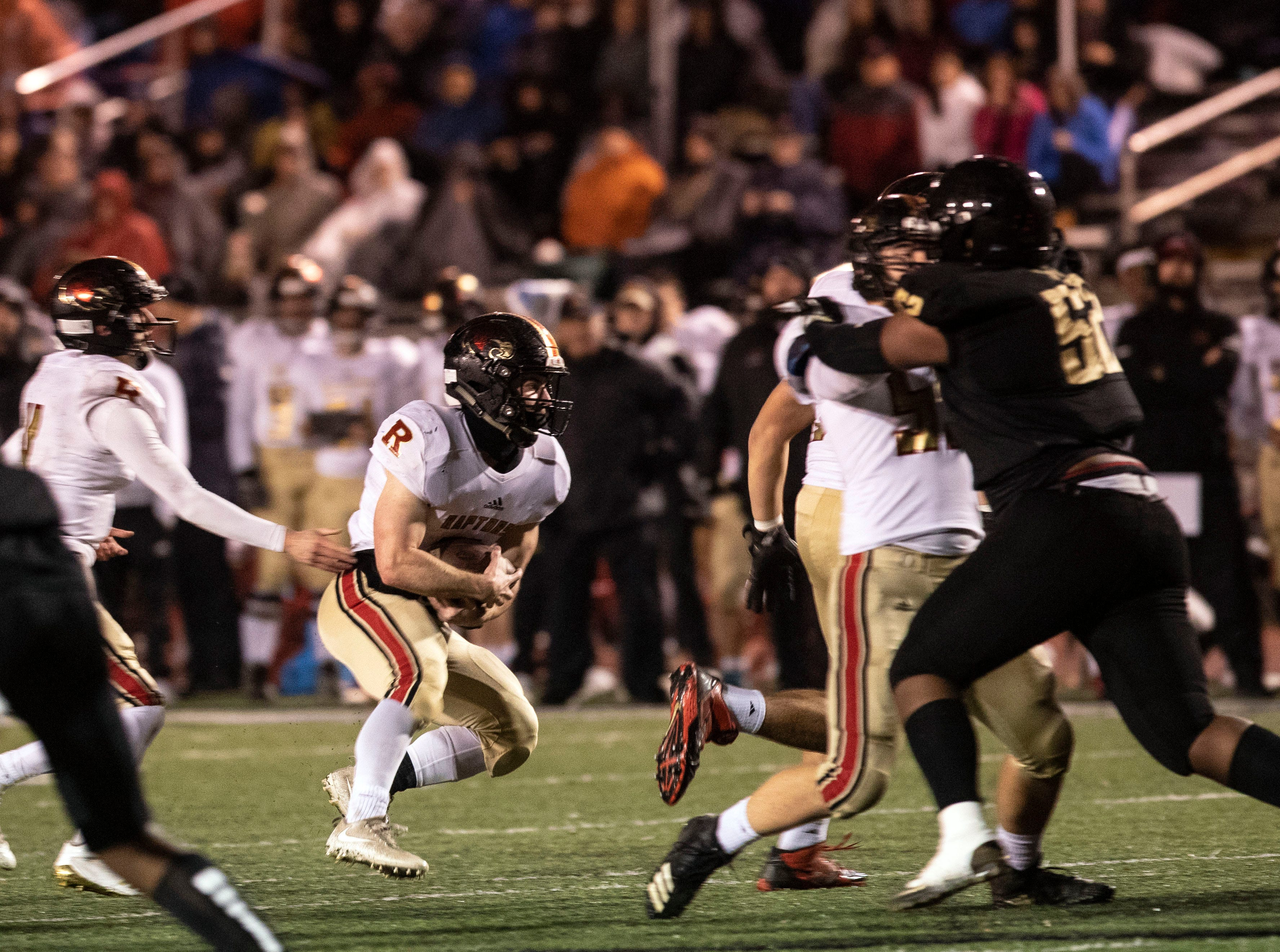 Ravenwood Raptors quarterback Brian Garcia (4) hands off to running back William Baine (8),  during the first half of a high school playoff football game, Friday, Nov. 23, 2018.