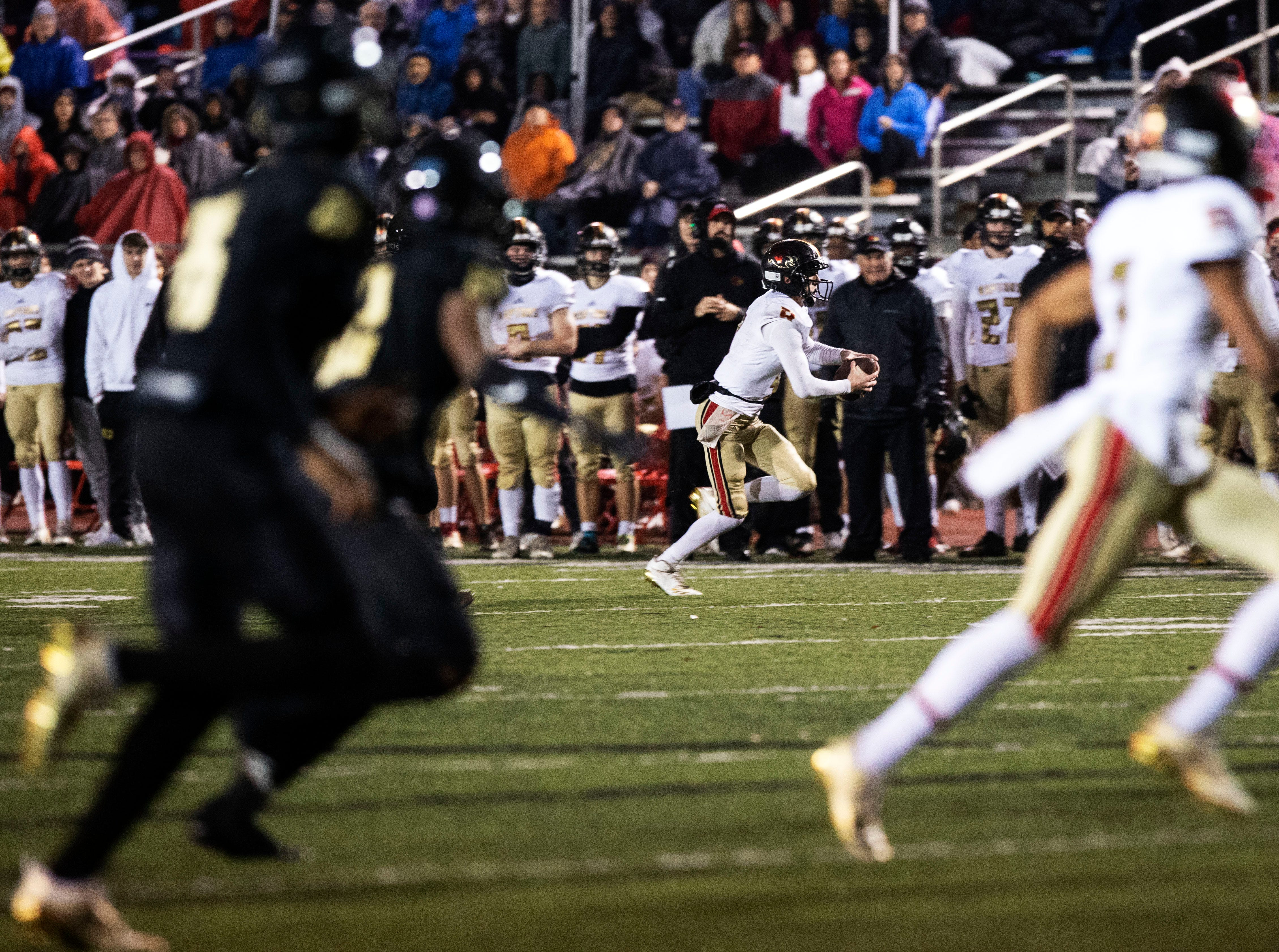 Ravenwood Raptors quarterback Brian Garcia (4)  runs out of bounds against Whitehaven Tigers defenders during the first half of an high school playoff football game, Friday, Nov. 23, 2018.