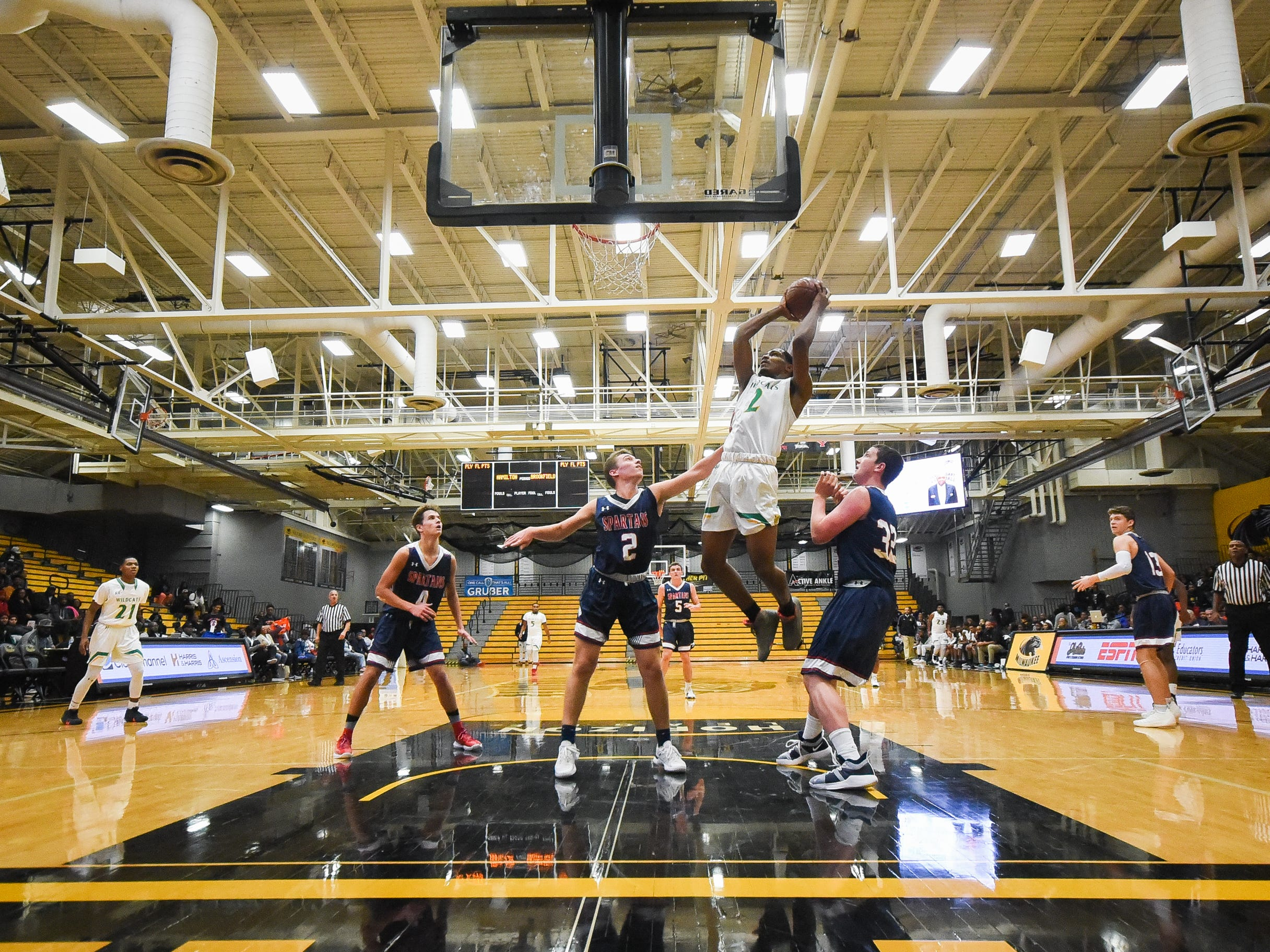 Milwaukee Hamilton sophomore forward Antoine Taylor goes up for a shot between Brookfield East defenders Micheal Poker (2) and Riley LeTourneau in the Fresh Coast Classic high school basketball showcase Saturday, November 24, 2018, at UW-Milwaukee's Klotsche Center.