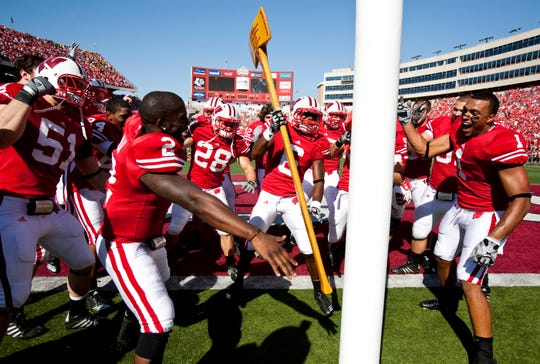 Badgers' Jay Valai swings the Paul Bunyan Axe surrounded by his teammates after the homecoming game with Minnesota in 2010.