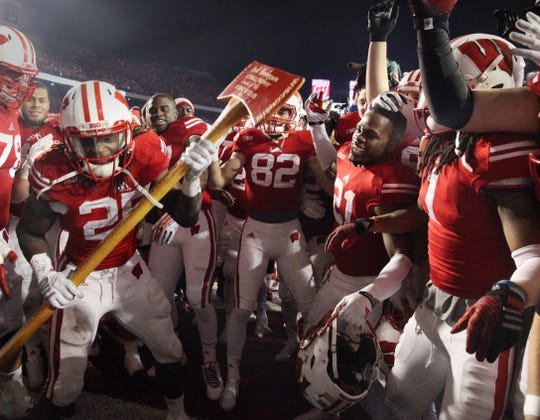 Wisconsin Badgers running back Melvin Gordon (25) wields the Paul Bunyan Axe as he pretends to chop down the goal post amid cheering teammates in 2014.