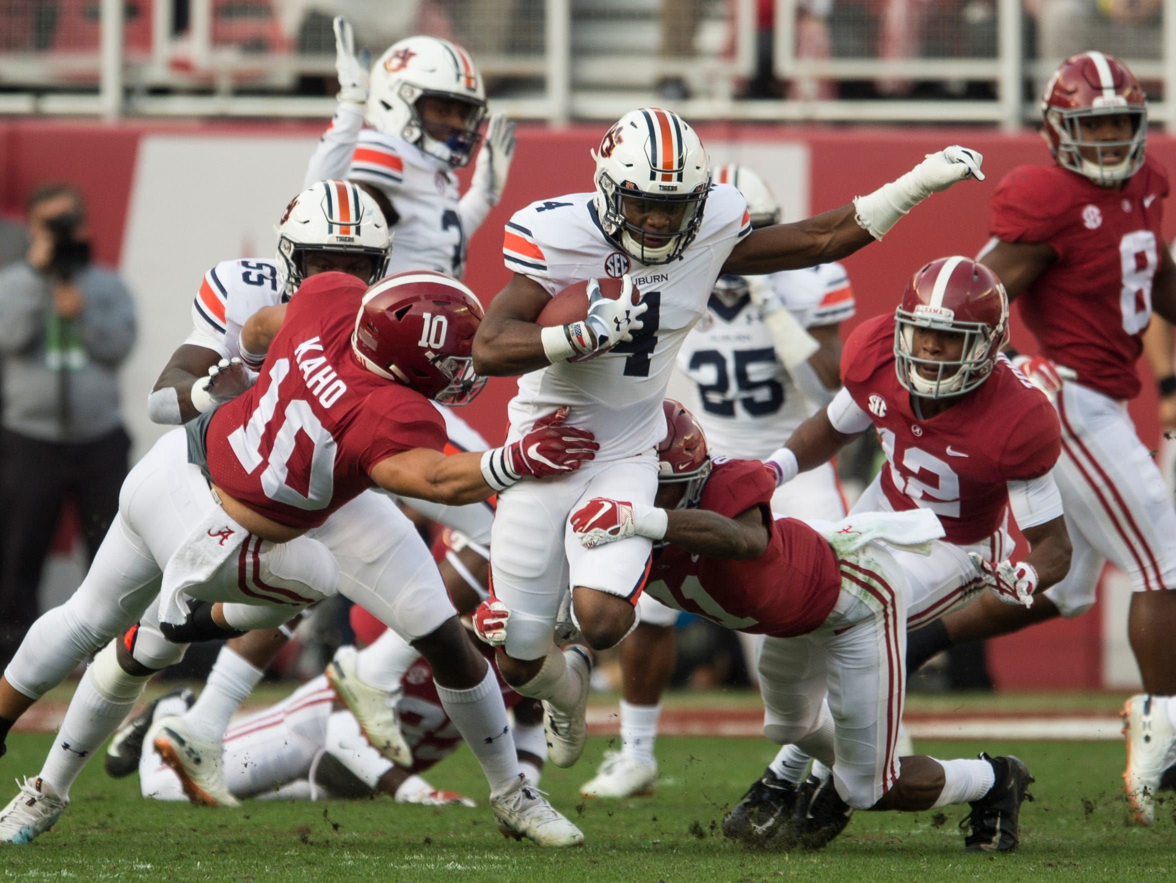Auburn defensive back Noah Igbinoghene (4) is taken down as he returns a kick off during the Iron Bowl at Bryant-Denny Stadium in Tuscaloosa, Ala., on Saturday, Nov. 24, 2018. Alabama leads Auburn 17-14 at halftime.