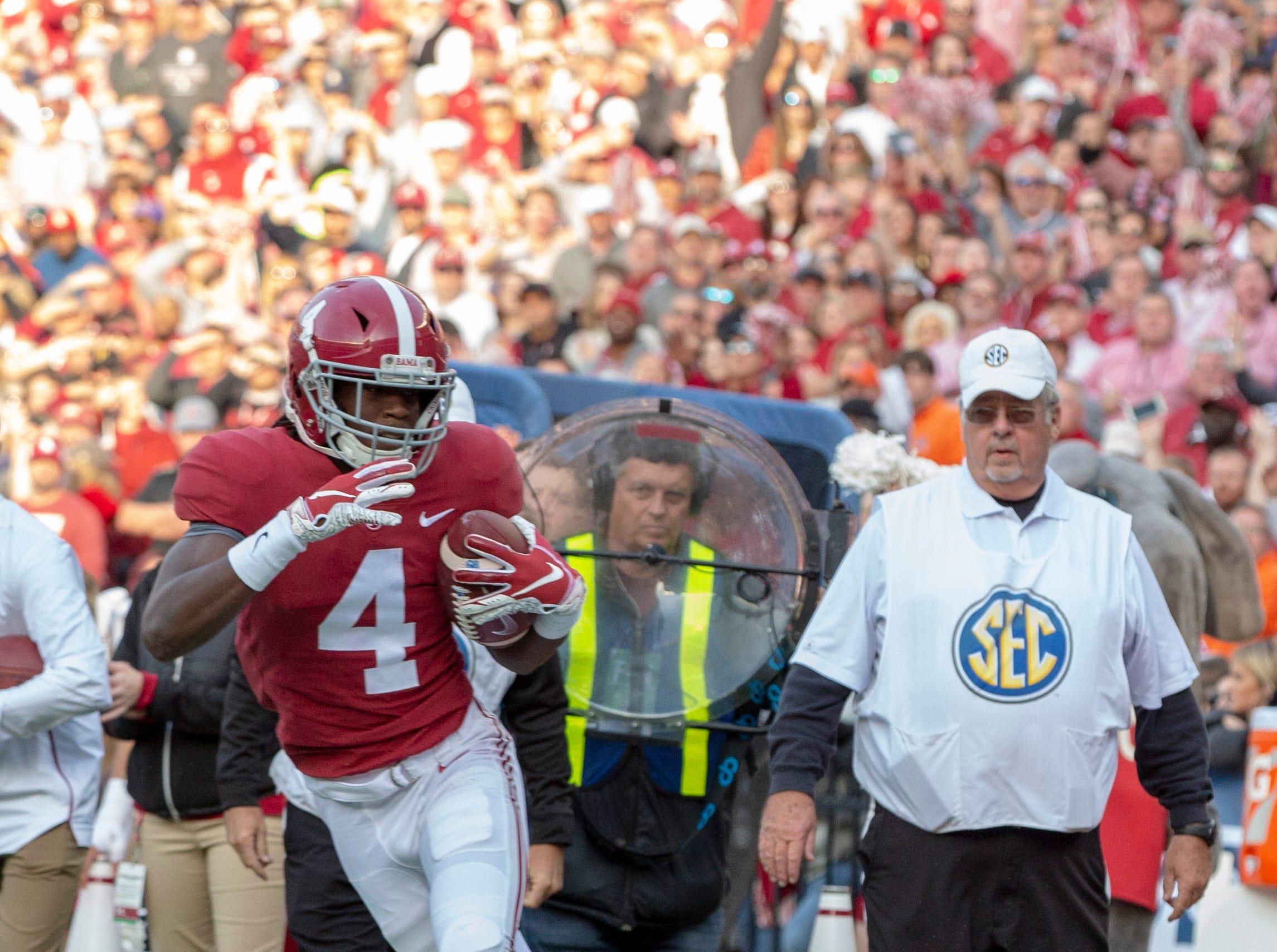 Alabama's Jerry Jeudy runs the ball as Auburn's Javaris Davis tries to take him down for a tackle.