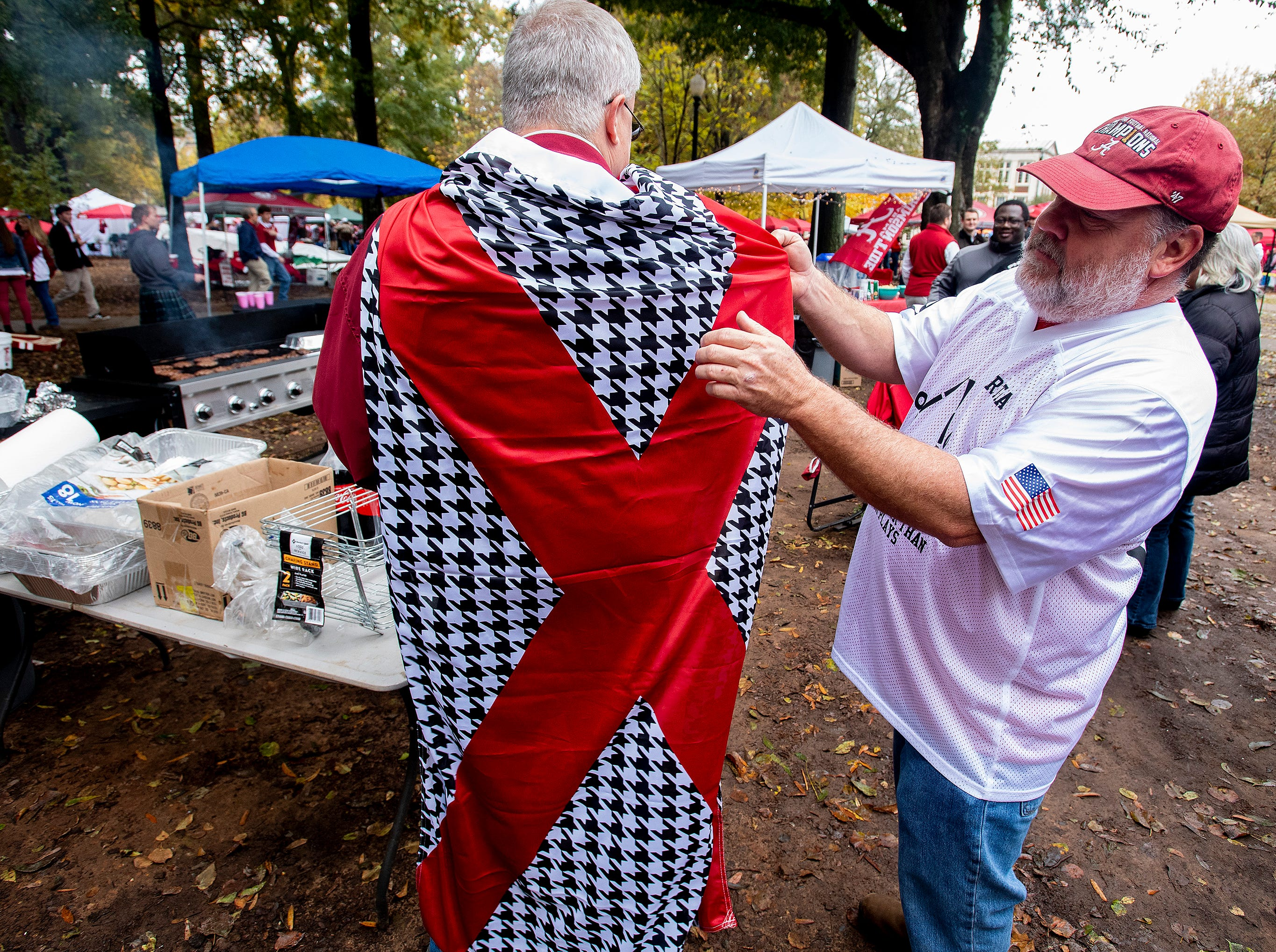 Joe Geer adjusts the Alabama flag/cape of Alan Murr while tailgating before the Iron Bowl at  Bryant-Denny Stadium in Tuscaloosa, Ala., on Saturday November 24, 2018.