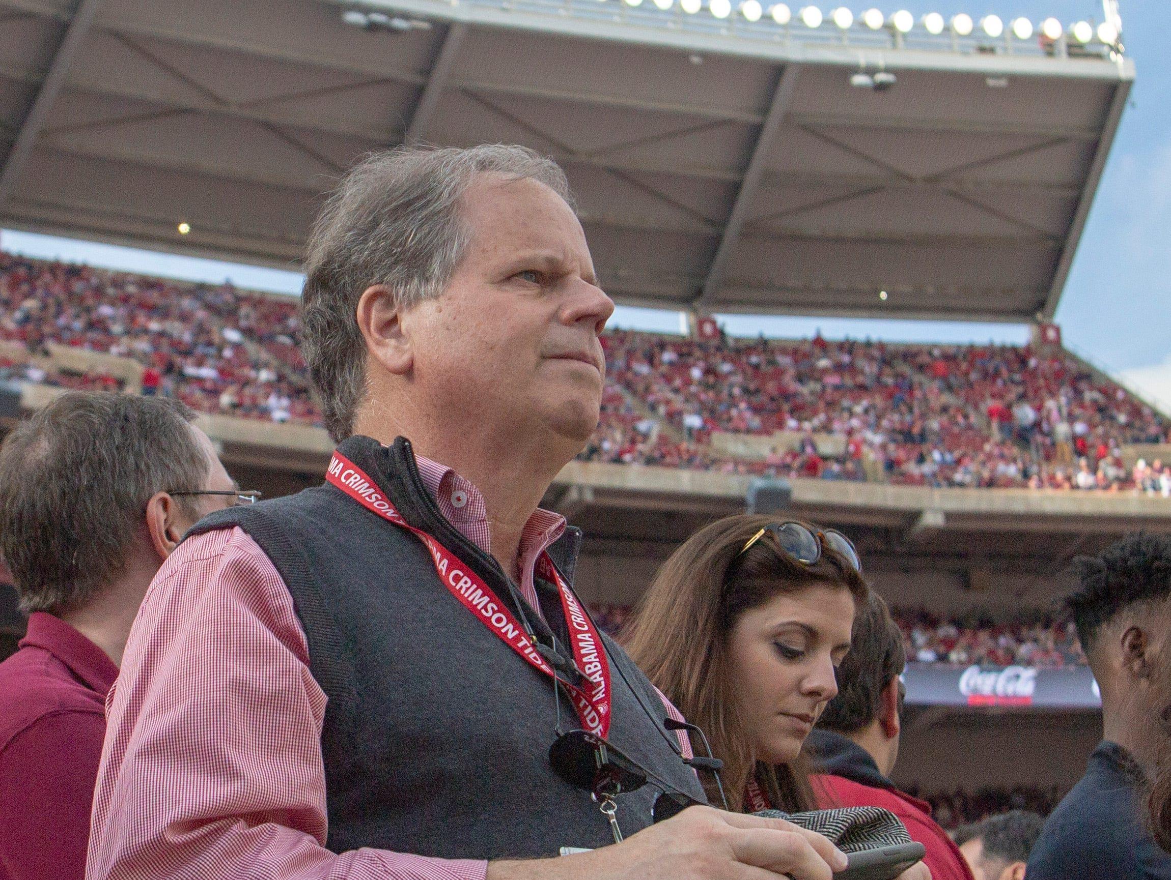 U.S. Sen. Doug Jones looks on as both Alabama and Auburn's football teams warm up before kickoff.