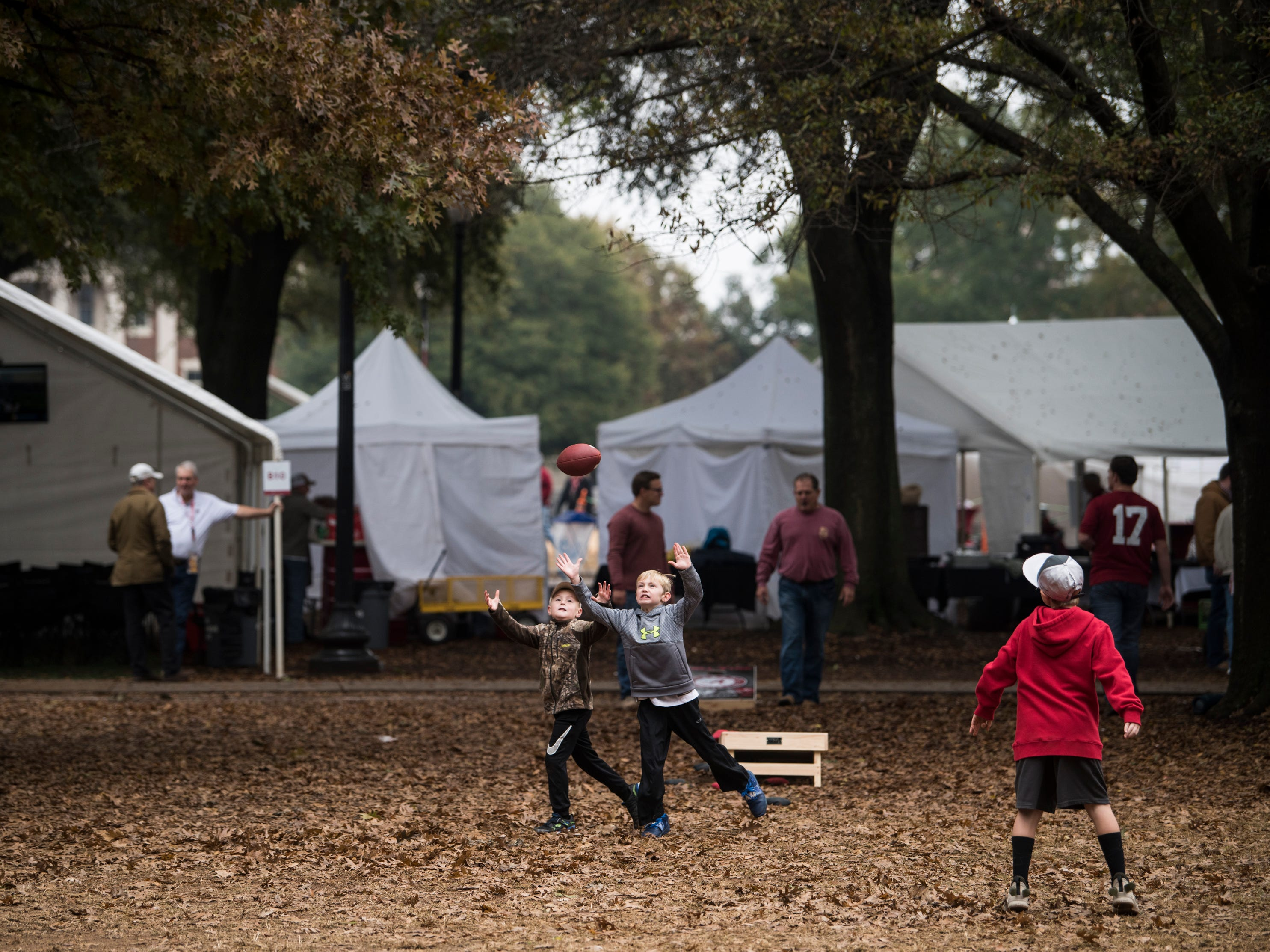 Fans toss around a football outside Bryant-Denny Stadium in Tuscaloosa, Ala., on Saturday, Nov. 24, 2018.