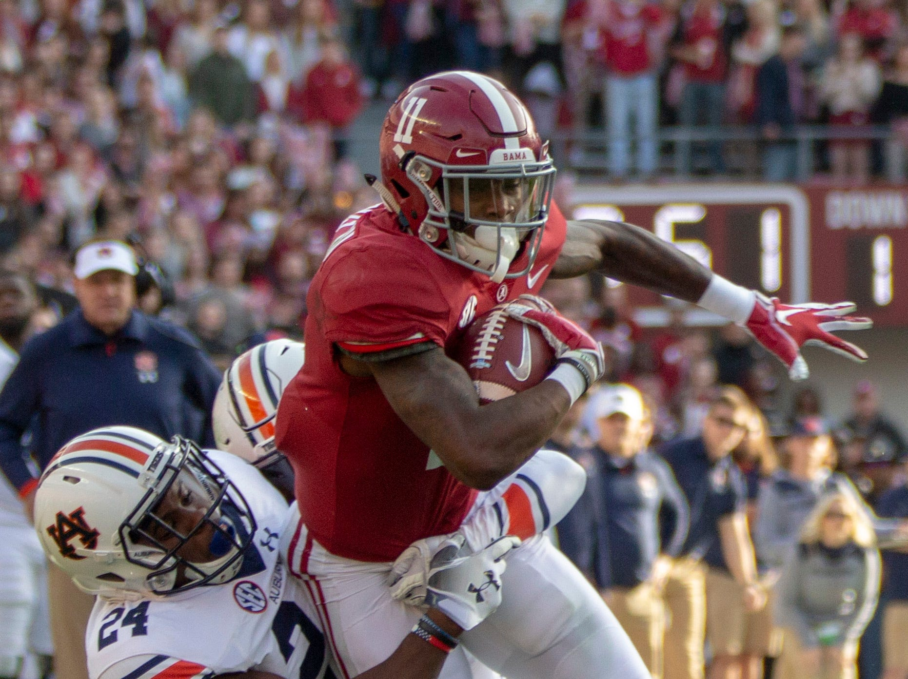 Alabama's Henry Ruggs III is brought down by Auburn's Daniel Thomas during a play in the first quarter.
