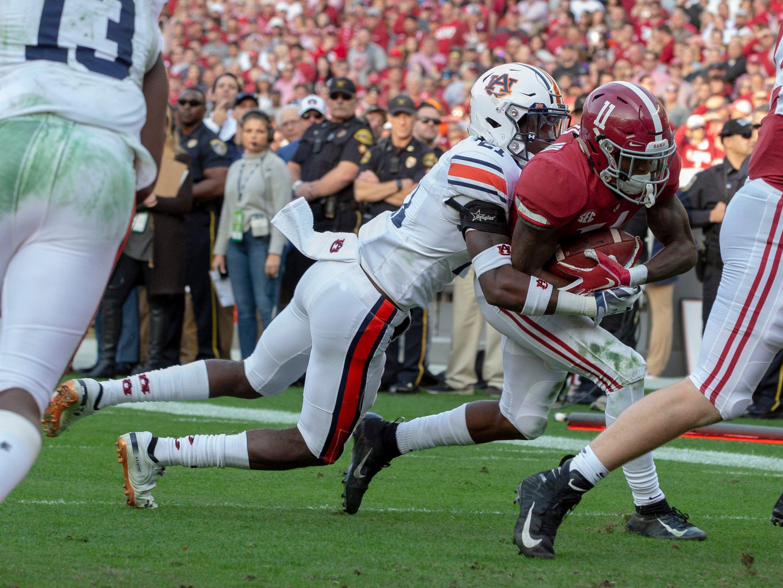 Alabama's Henry Ruggs III runs the ball as Auburn's Smoke Monday tries to take him down.