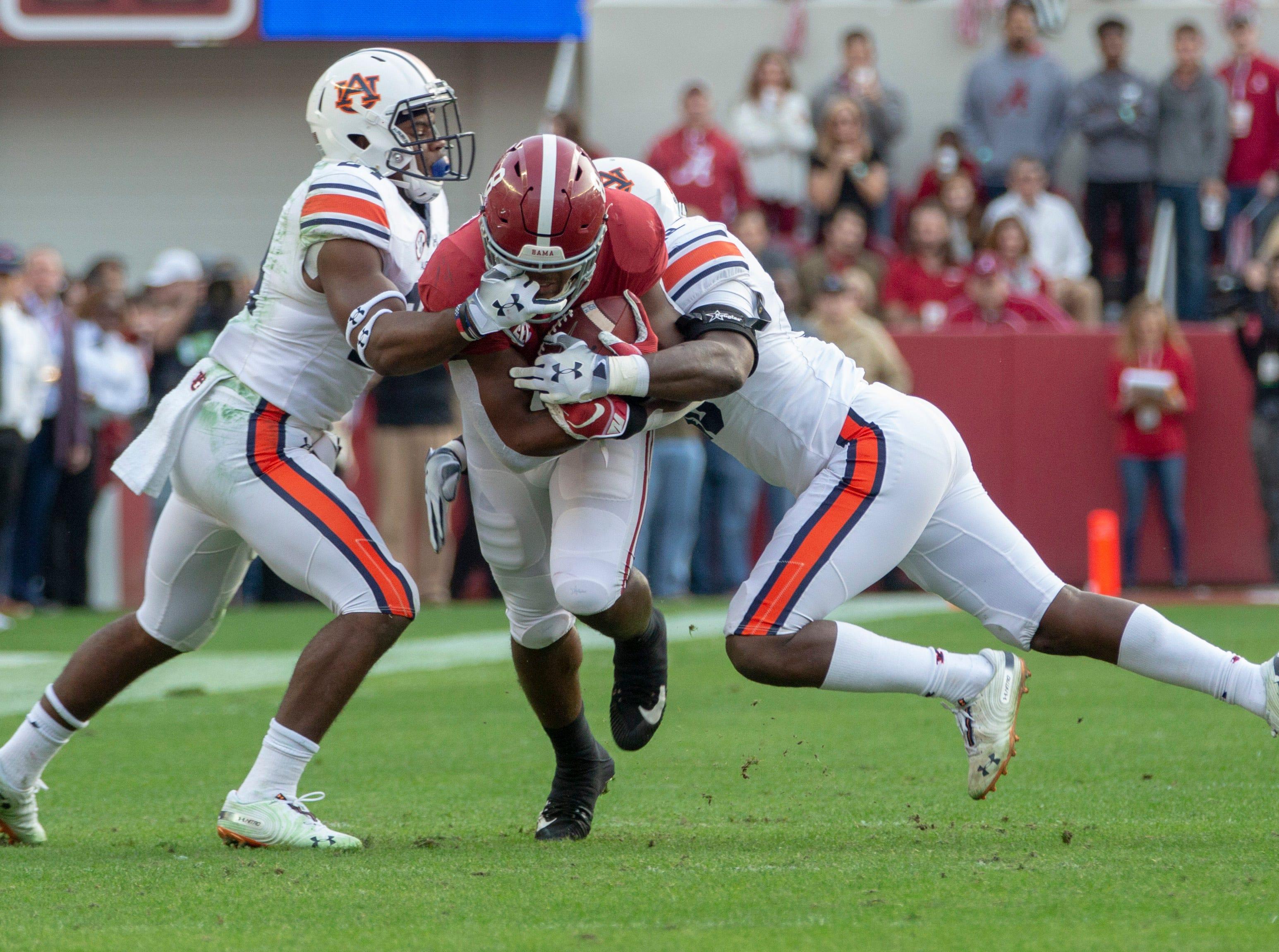 Alabama's Josh Jacobs runs the ball as Auburn's Daniel Thomas grabs his facemark of his helmet.