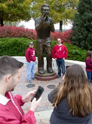 Alabama fans take photos with a statue of Nick Saban outside of the stadium before the Iron Bowl.