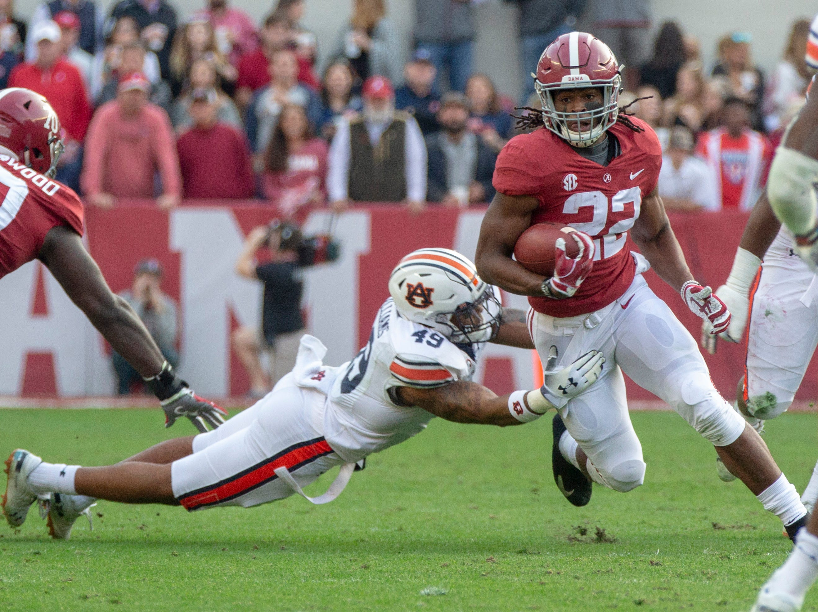 Alabama's Najee Harris runs the ball as he tries to avoid a tackle by Auburn's Darrell Williams.
