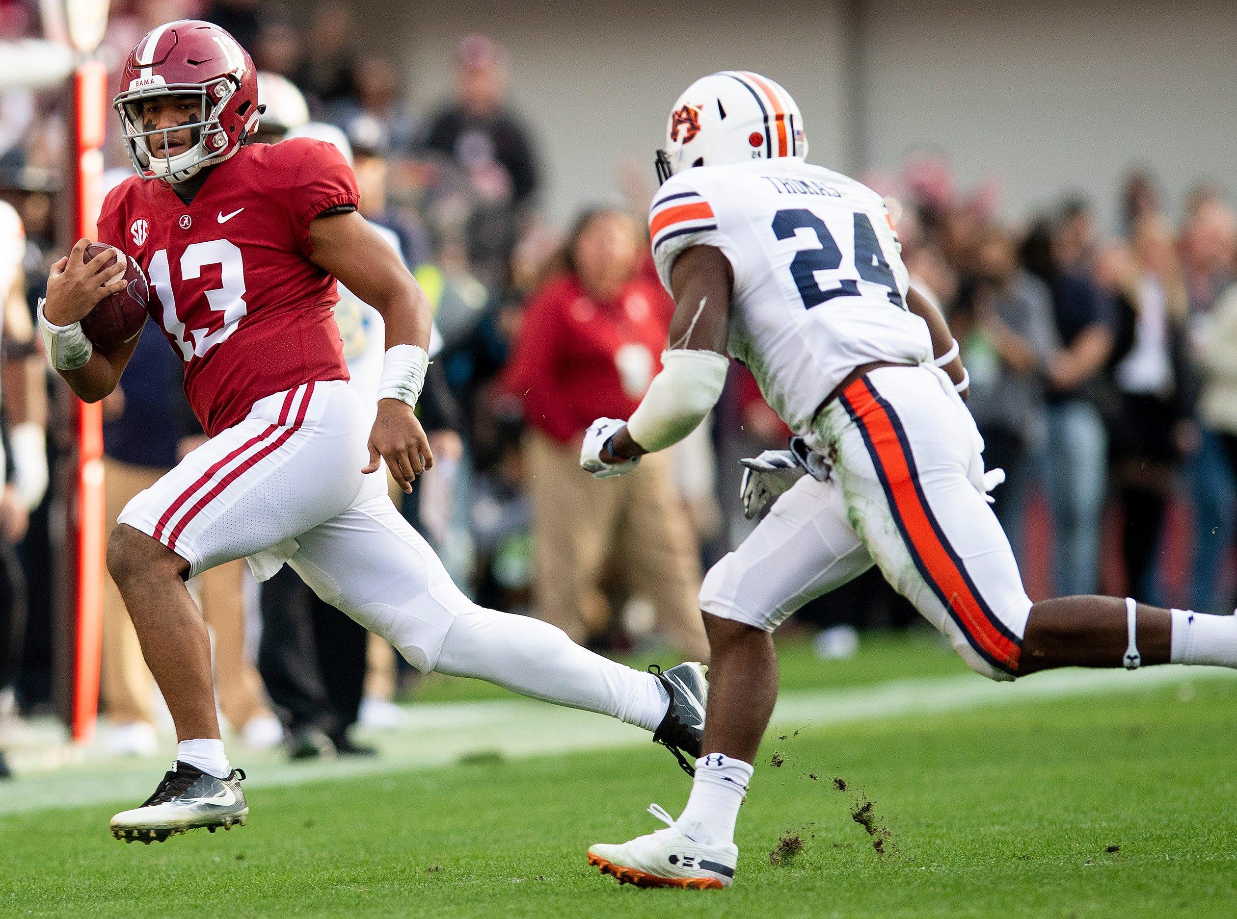 Alabama quarterback Tua Tagovailoa (13) eludes Auburn defensive back Daniel Thomas (24) in first half action during the Iron Bowl at Bryant-Denny Stadium in Tuscaloosa, Ala., on Saturday November 24, 2018.