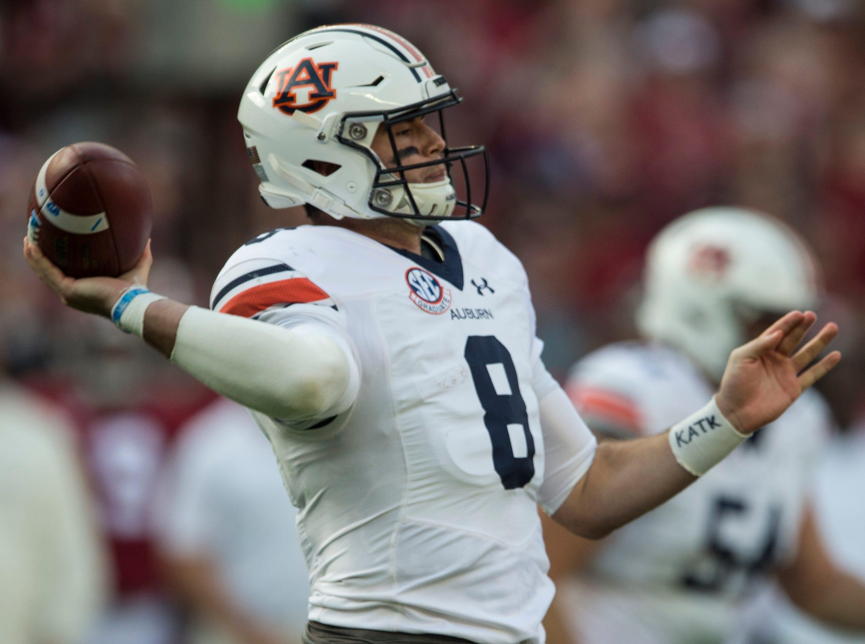 Auburn quarterback Jarrett Stidham (8) throws the ball down field during the Iron Bowl at Bryant-Denny Stadium in Tuscaloosa, Ala., on Saturday, Nov. 24, 2018. Alabama leads Auburn 17-14 at halftime.