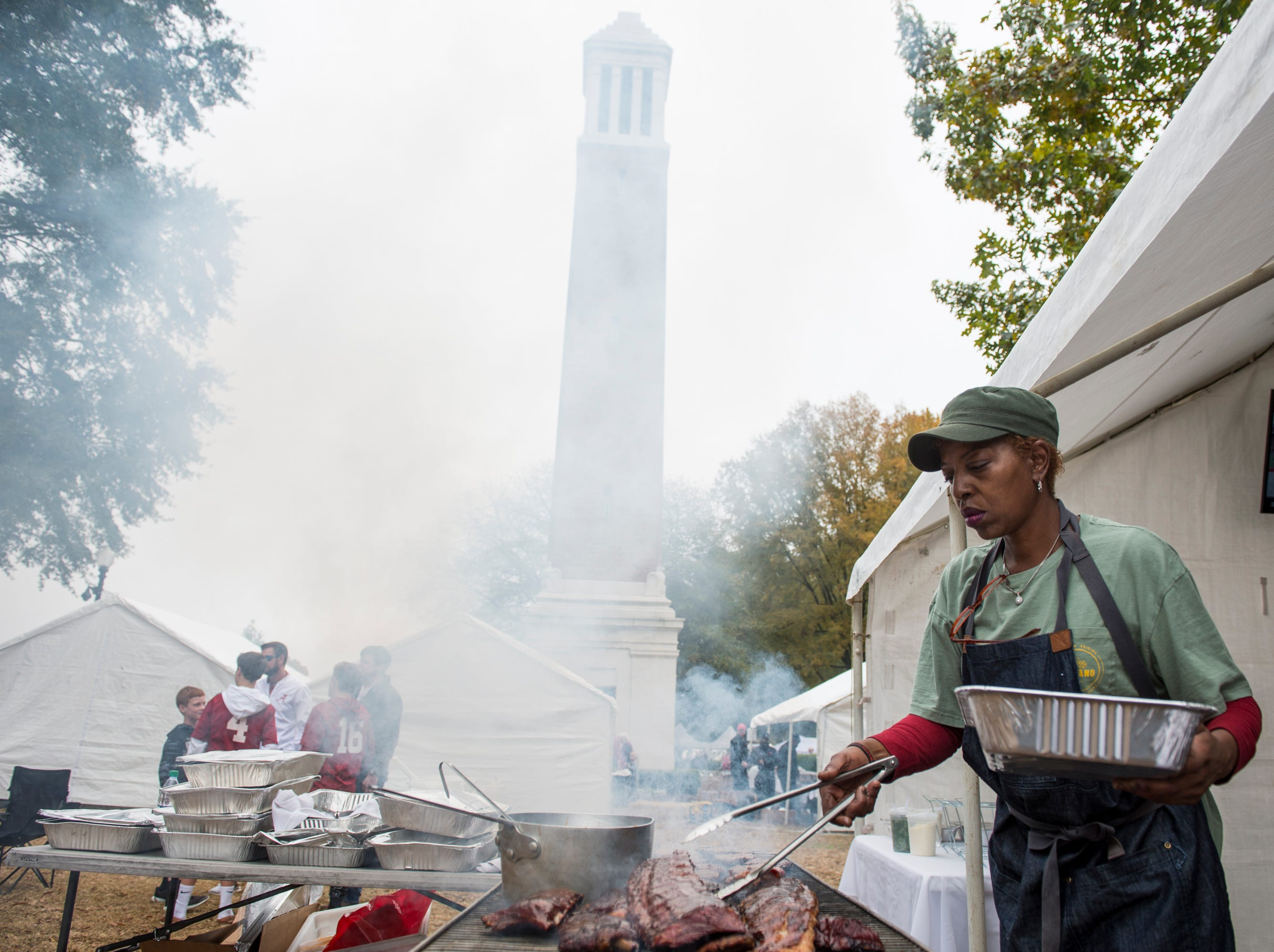 Tessie Thomas cooks up some tailgate food on the grill outside Bryant-Denny Stadium in Tuscaloosa, Ala., on Saturday, Nov. 24, 2018.