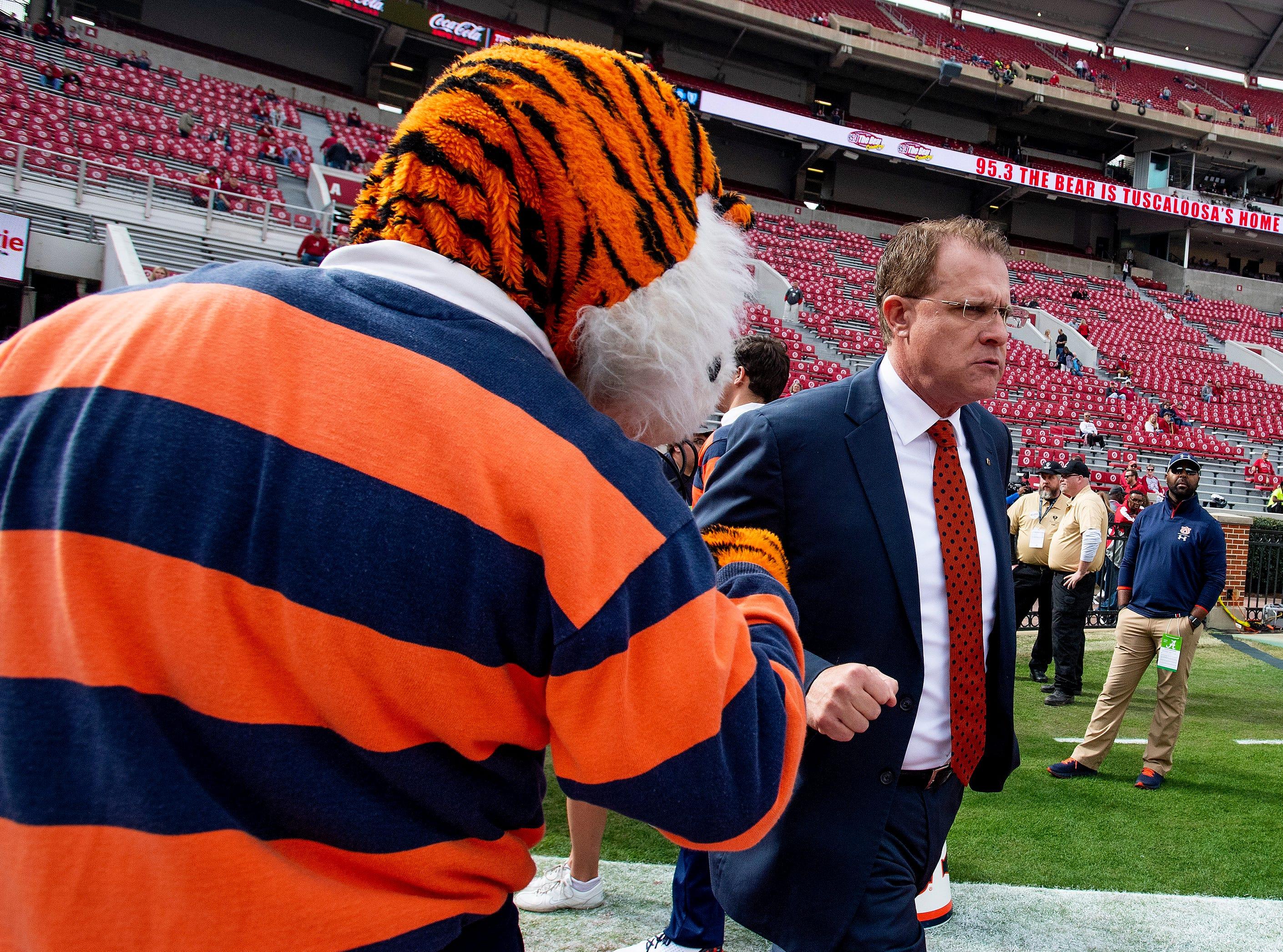 Auburn head coach Gus Malzahn fist bumps Auburn mascot Aubie as Auburn arrives at Bryant-Denny Stadium in Tuscaloosa, Ala., before the Iron Bowl on Saturday November 24, 2018.