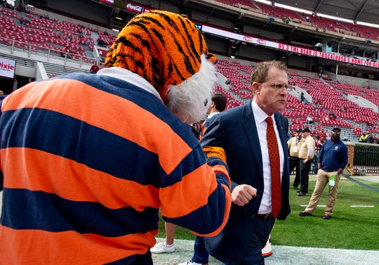 Auburn head coach Gus Malzahn fist bumps Auburn mascot Aubie as Auburn arrives at Bryant-Denny Stadium in Tuscaloosa, Ala., before the Iron Bowl on Saturday November 24, 2018.