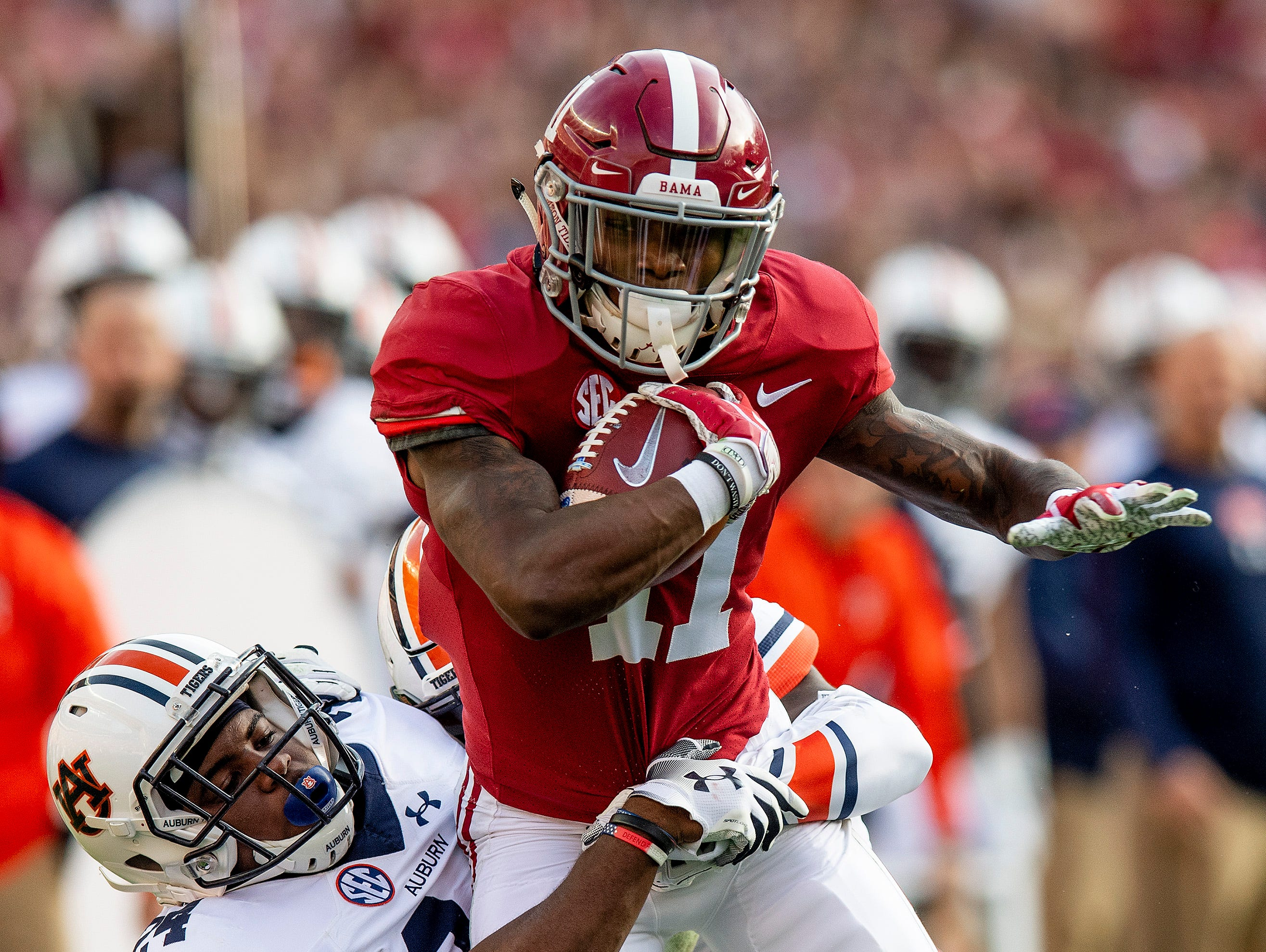 Alabama wide receiver Henry Ruggs, III, (11) is stopped by Auburn defensive back Daniel Thomas (24) in first half action during the Iron Bowl at Bryant-Denny Stadium in Tuscaloosa, Ala., on Saturday November 24, 2018.