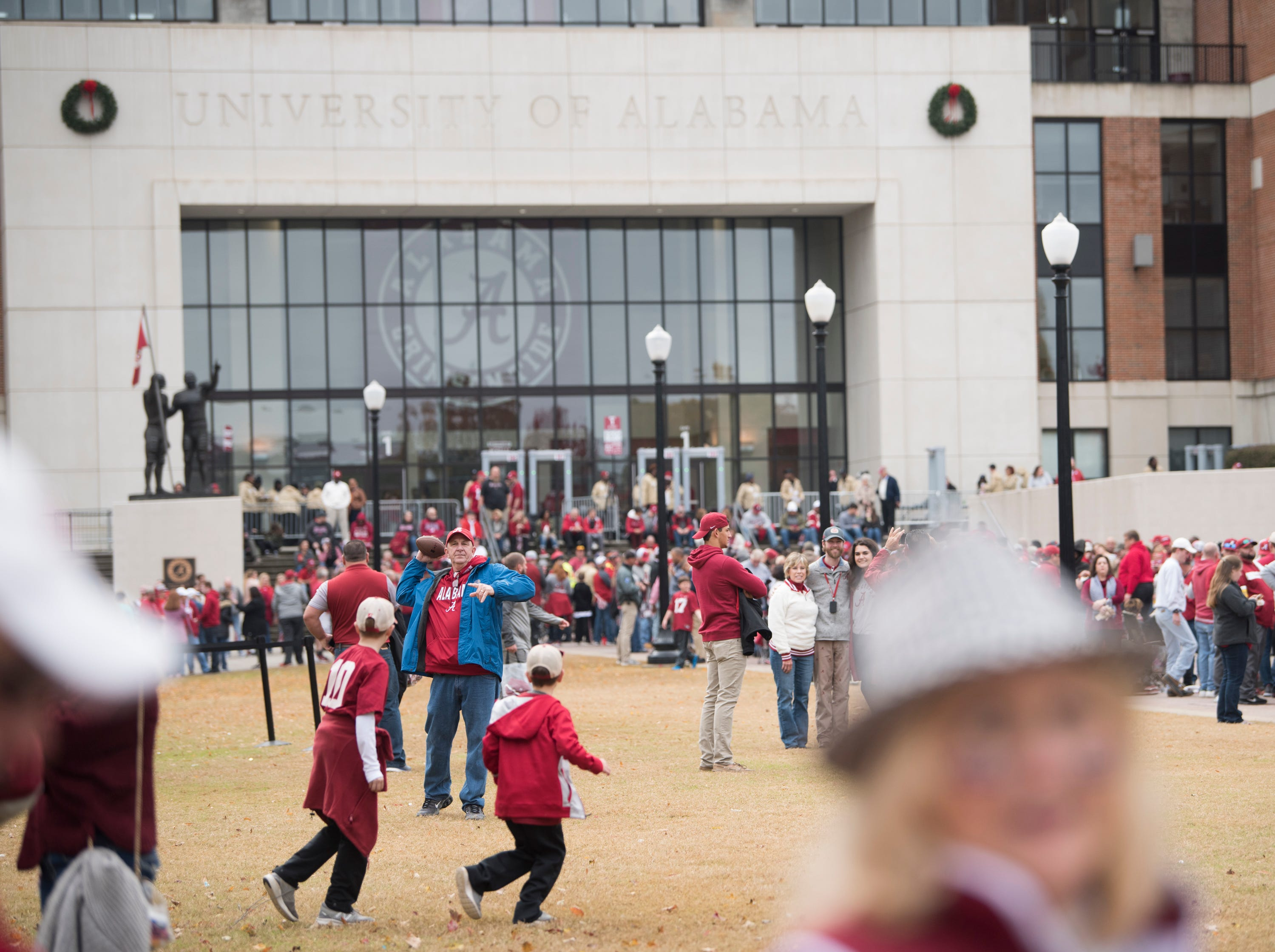 Fans play with a football outside Bryant-Denny Stadium in Tuscaloosa, Ala., on Saturday, Nov. 24, 2018.