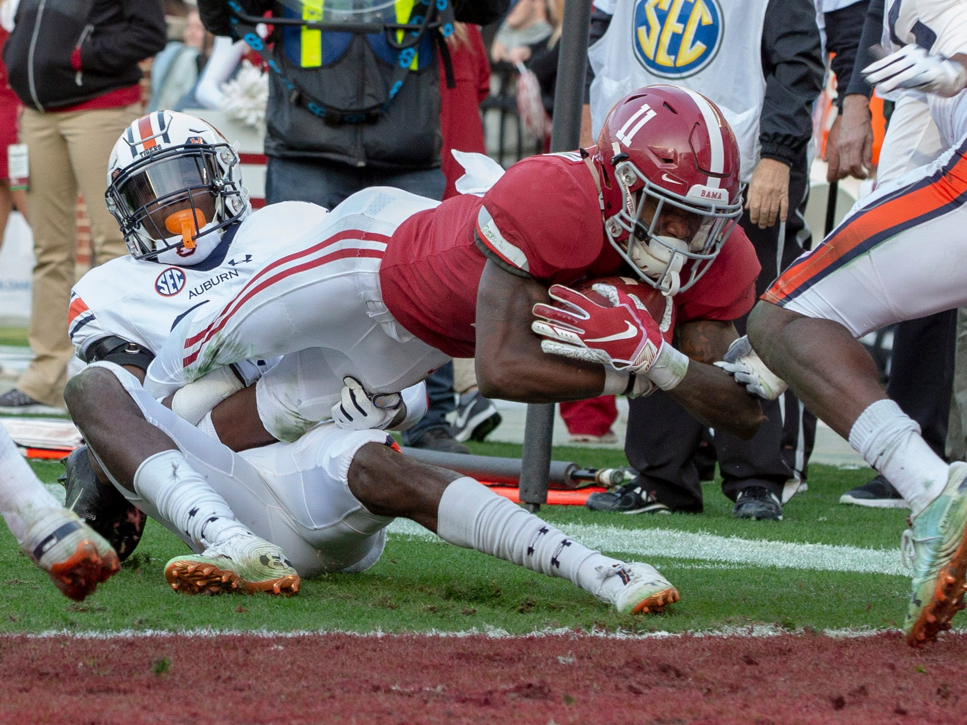 Alabama's Henry Ruggs III manages a touchdown in the second quarter as Auburn's Smoke Monday tries to take him down.