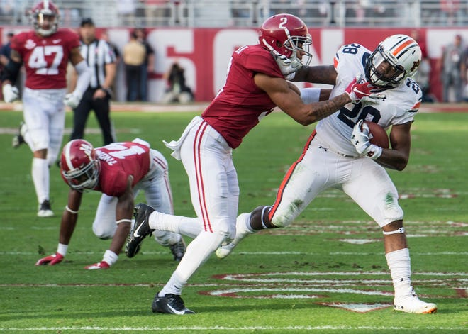 Auburn running back JaTarvious Whitlow (28) is tackled by Alabama defensive back Patrick Surtain, II, (2) during the Iron Bowl at Bryant-Denny Stadium in Tuscaloosa, Ala., on Saturday, Nov. 24, 2018. Alabama leads Auburn 17-14 at halftime.