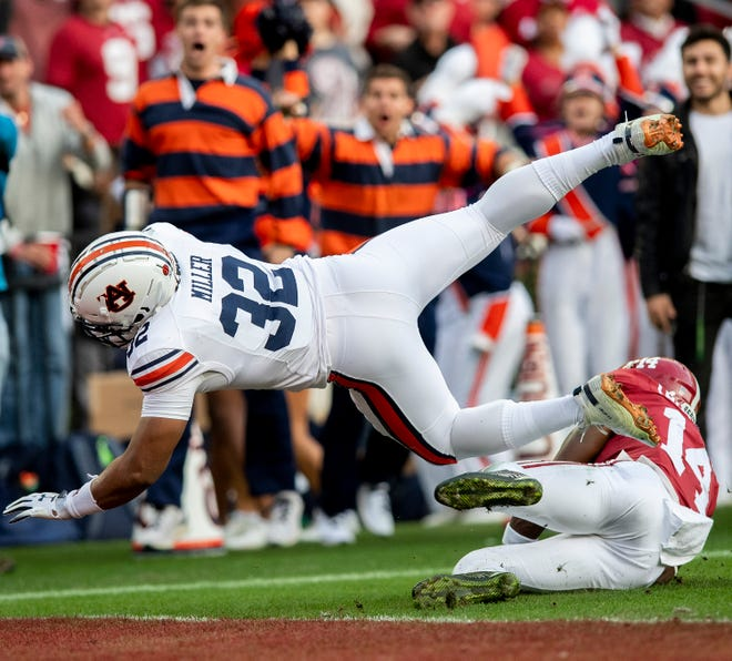 Auburn running back Malik Miller (32) dives in for a touchdown against Alabama defensive back Deionte Thompson (14) in first half action during the Iron Bowl at Bryant-Denny Stadium in Tuscaloosa, Ala., on Saturday November 24, 2018.