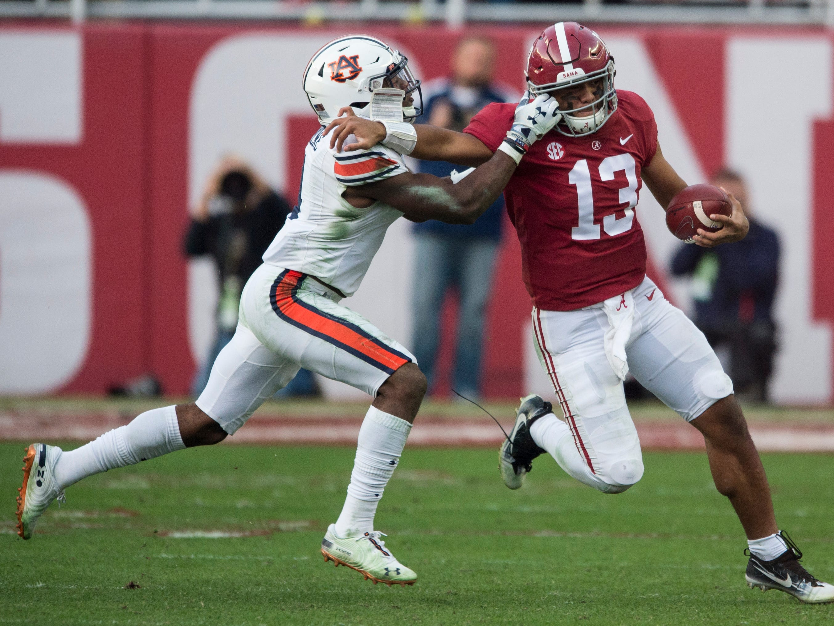 Alabama quarterback Tua Tagovailoa (13) is tackled by Auburn defensive back Noah Igbinoghene (4) during the Iron Bowl at Bryant-Denny Stadium in Tuscaloosa, Ala., on Saturday, Nov. 24, 2018. Alabama leads Auburn 17-14 at halftime. No face mask penalty was called on the play.