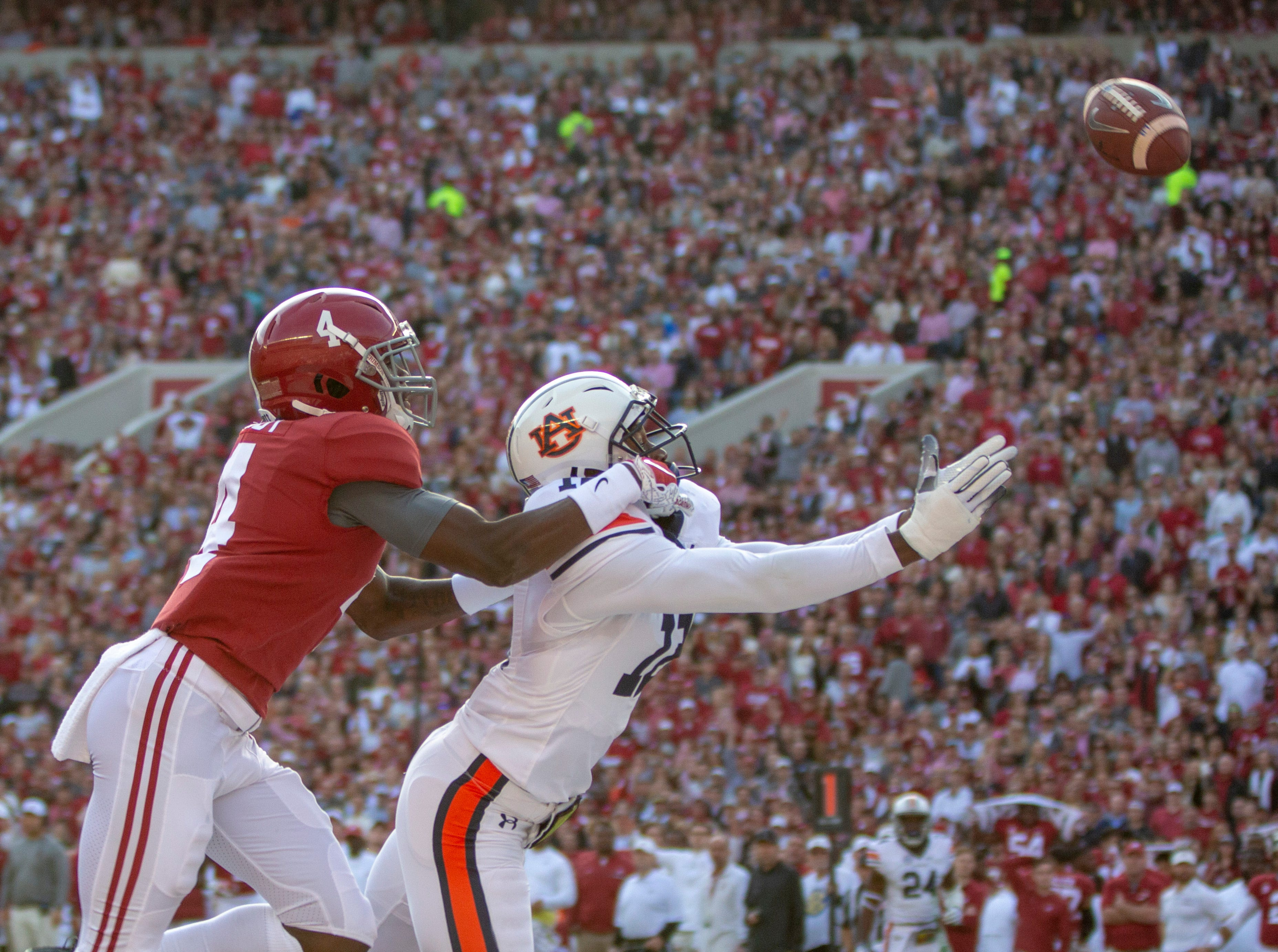 Alabama's Jerry Jeudy tries to keep Auburn's Jamel Dean from catching an interception in Bama's end zone.