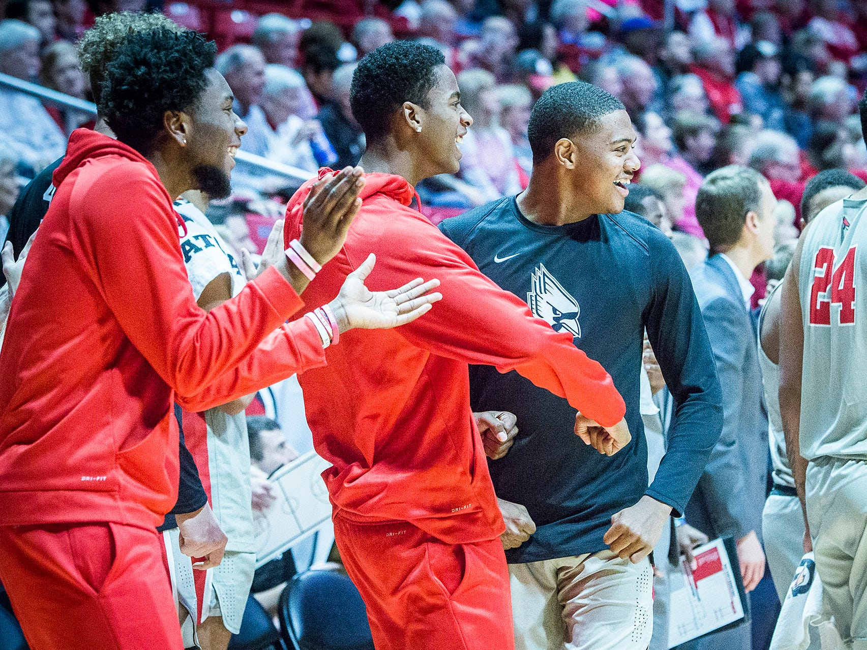 Ball State players Kani Acree (left), Miryne Thomas (center) and Jarron Coleman cheer on their teammates during a game against Evansville at Worthen Arena Saturday, Nov. 24, 2018.