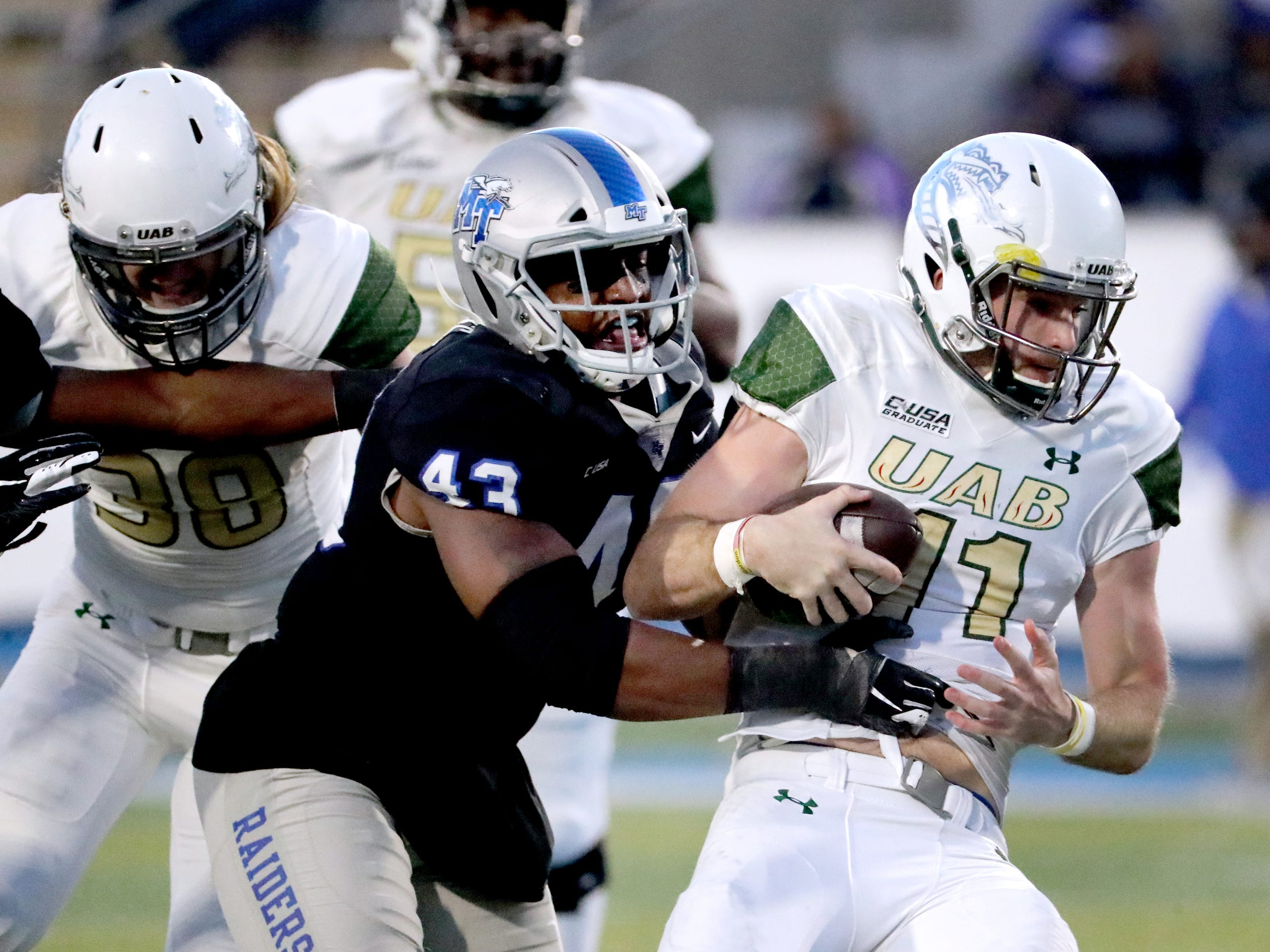MTSU's () runs the ball as he is tackled by UAB's () during the game at MTSU on Saturday, Nov. 24, 2018.