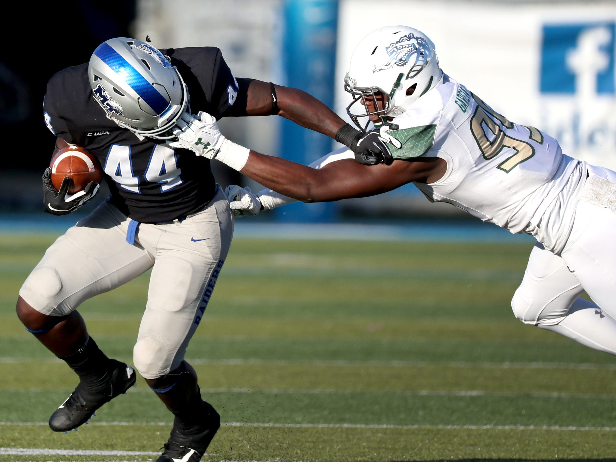 MTSU's Chaton Mobley 44) runs the ball as he is tackled and face masked by UAB's James Garcia-Williams (99) during the game at MTSU on Saturday, Nov. 24, 2018.