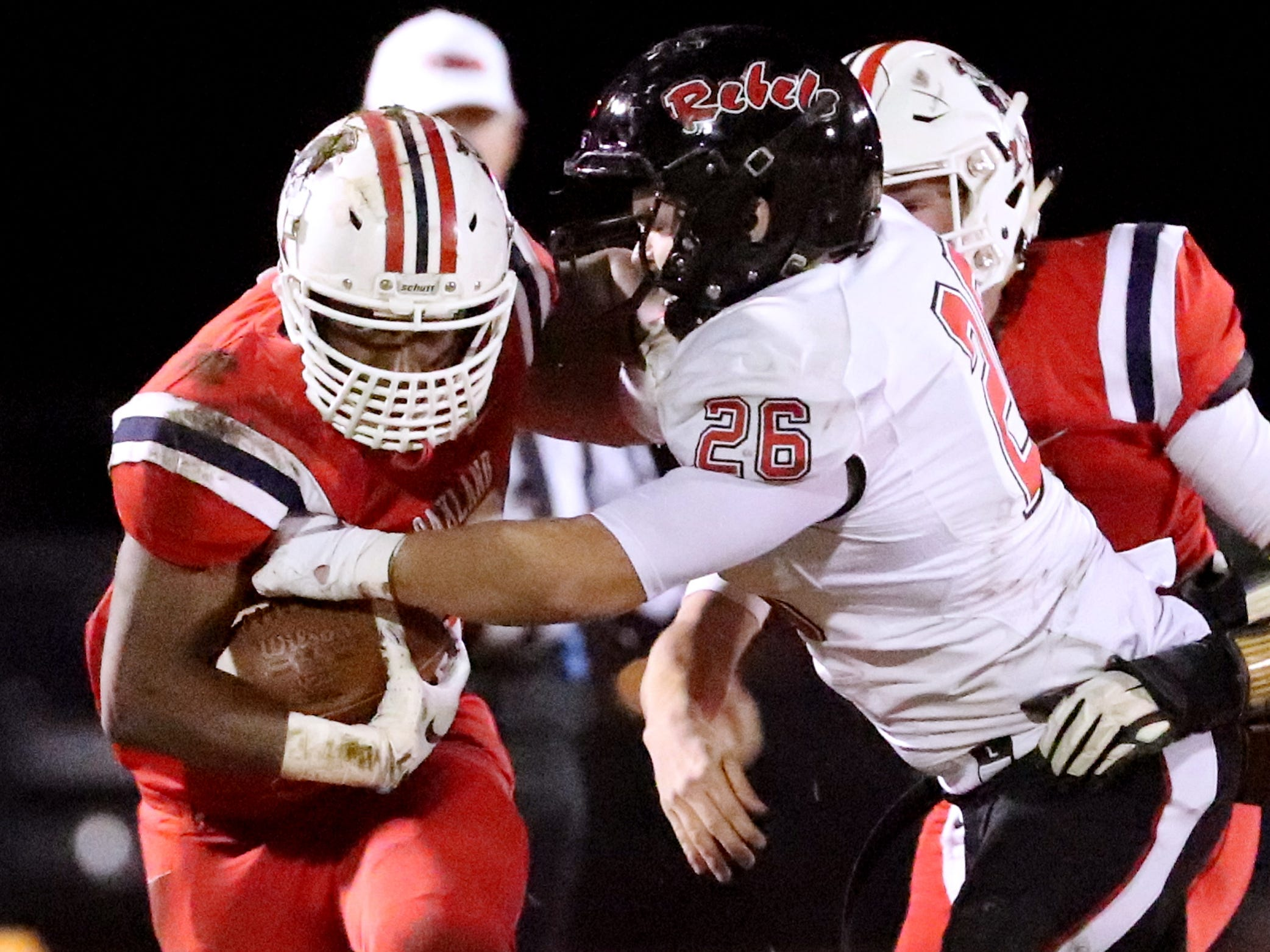 Oakland's Xavier Myers (26) runs the ball as Maryville's Seth Orren (26) moves in for a tackle at Oakland in Murfreesboro, on Friday, Aug. 23 2018, during the 6A playoffs.