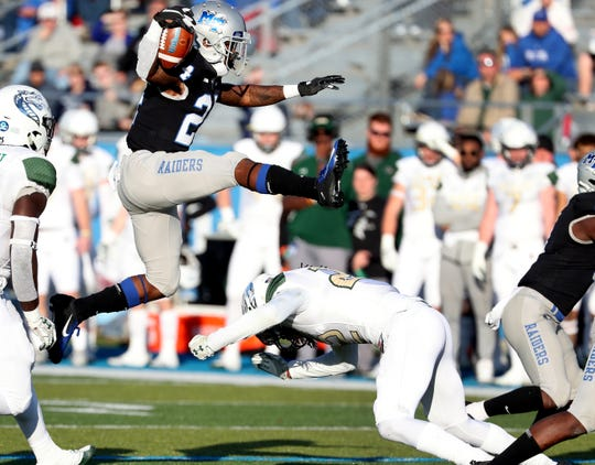 MTSU's Zack Dobson (24) runs the ball and leaps over UAB'sBroderick Thomas (22) during the game at MTSU on Saturday, Nov. 24, 2018.