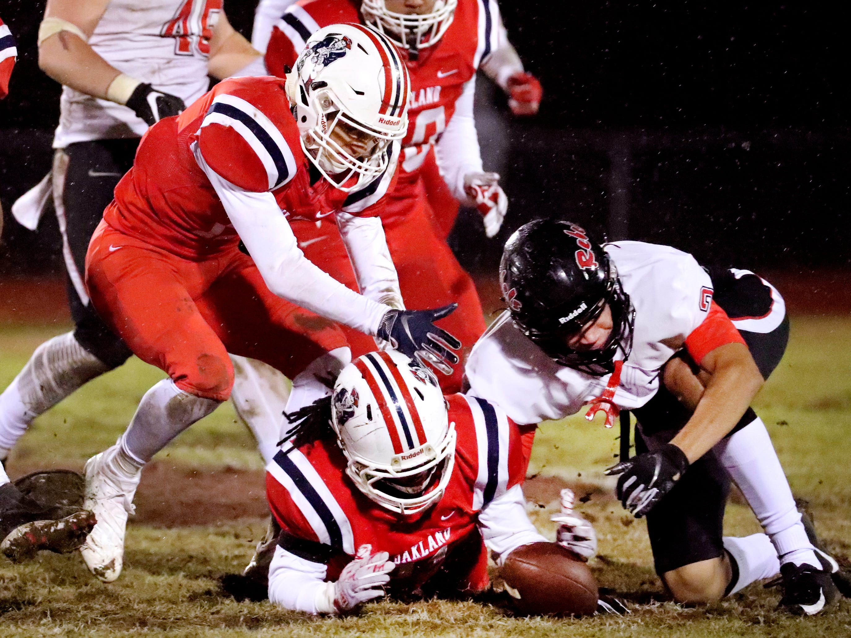 Oakland's Malik Sibert (11) recovers a fumble made by Maryville as Maryville's Ashton Maples (2) and Oakland's Eddie Willis (17) also try to recover the fumble at Oakland in Murfreesboro, on Friday, Aug. 23 2018, during the 6A playoffs.