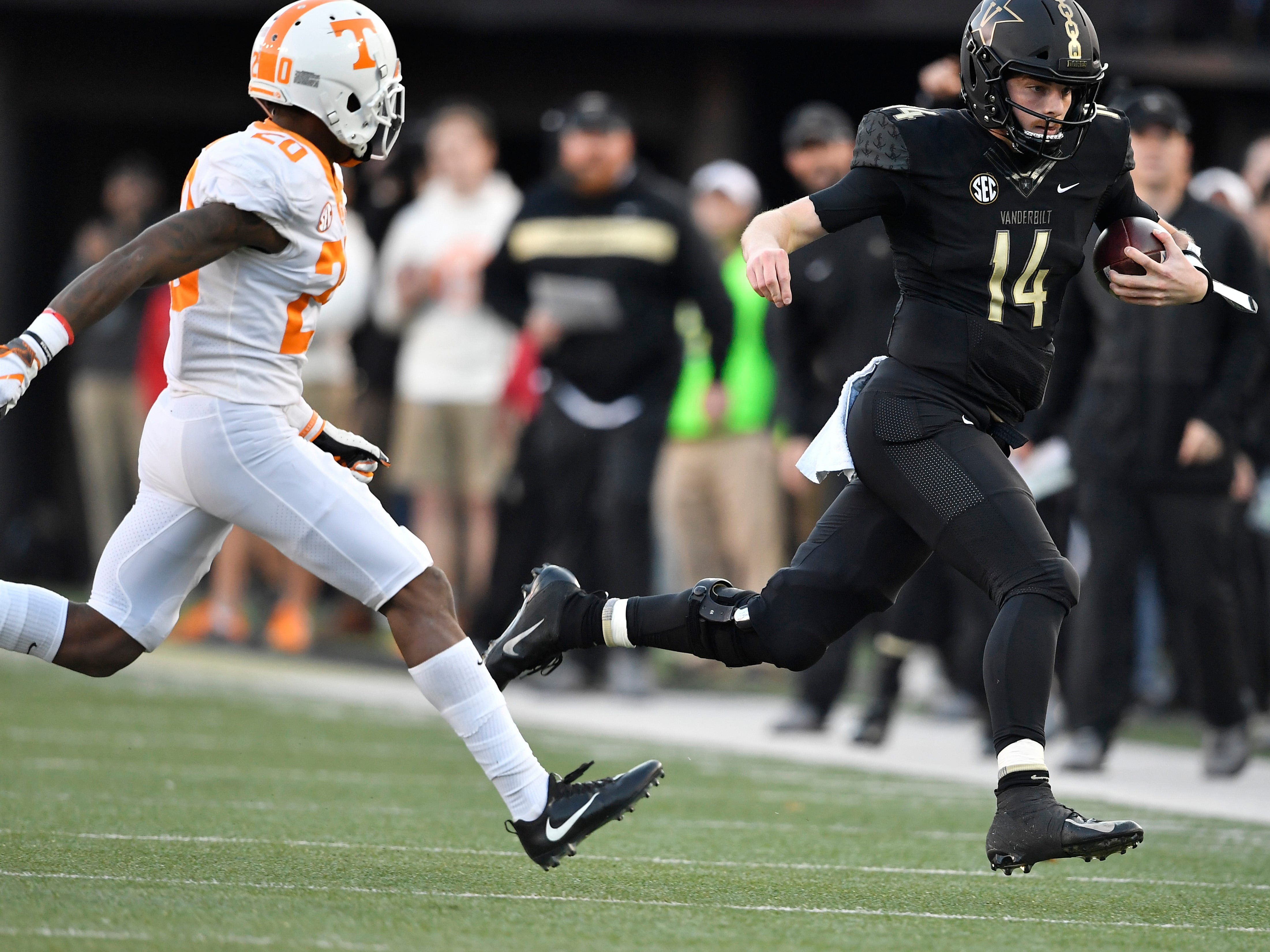 Vanderbilt quarterback Kyle Shurmur (14) scrambles for a first down defended by Tennessee defensive back Bryce Thompson (20) in the first half  at Vanderbilt Stadium Saturday, Nov. 24, 2018, in Nashville, Tenn.