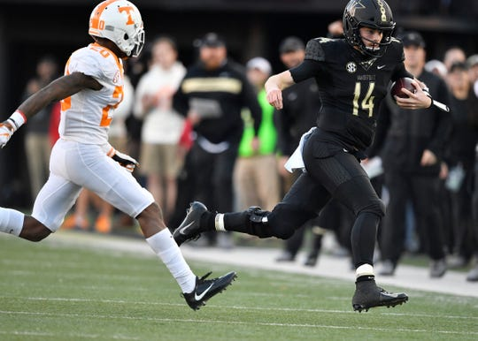 Vanderbilt quarterback Kyle Shurmur (14) scrambles for a first down defended by Tennessee defensive back Bryce Thompson (20) in the first half  at Vanderbilt Stadium Saturday, Nov. 24, 2018, in Nashville, Tenn.