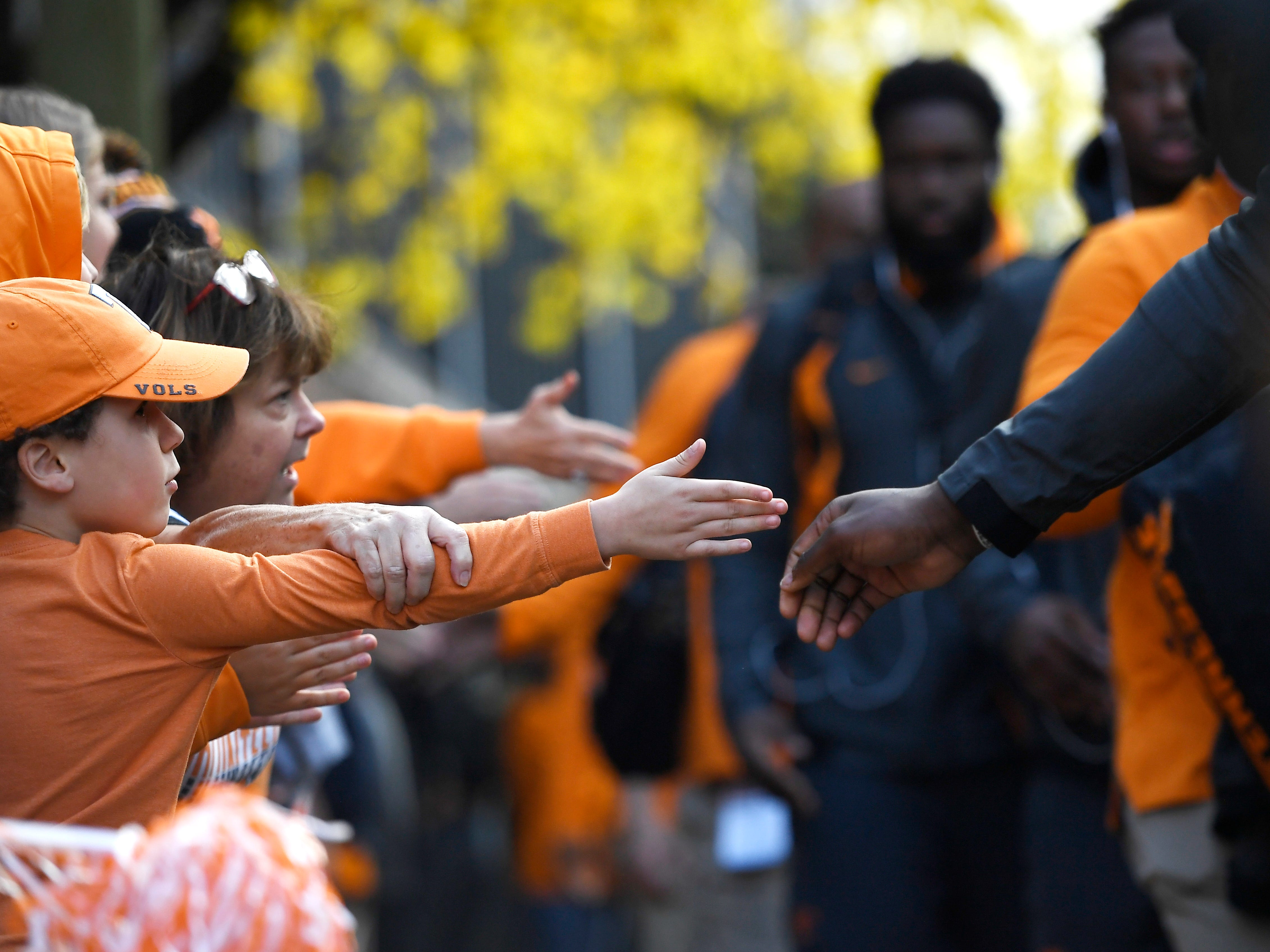 Tennessee fans slap hands with players as they arrive for the game at Vanderbilt Stadium Saturday, Nov. 24, 2018, in Nashville, Tenn.