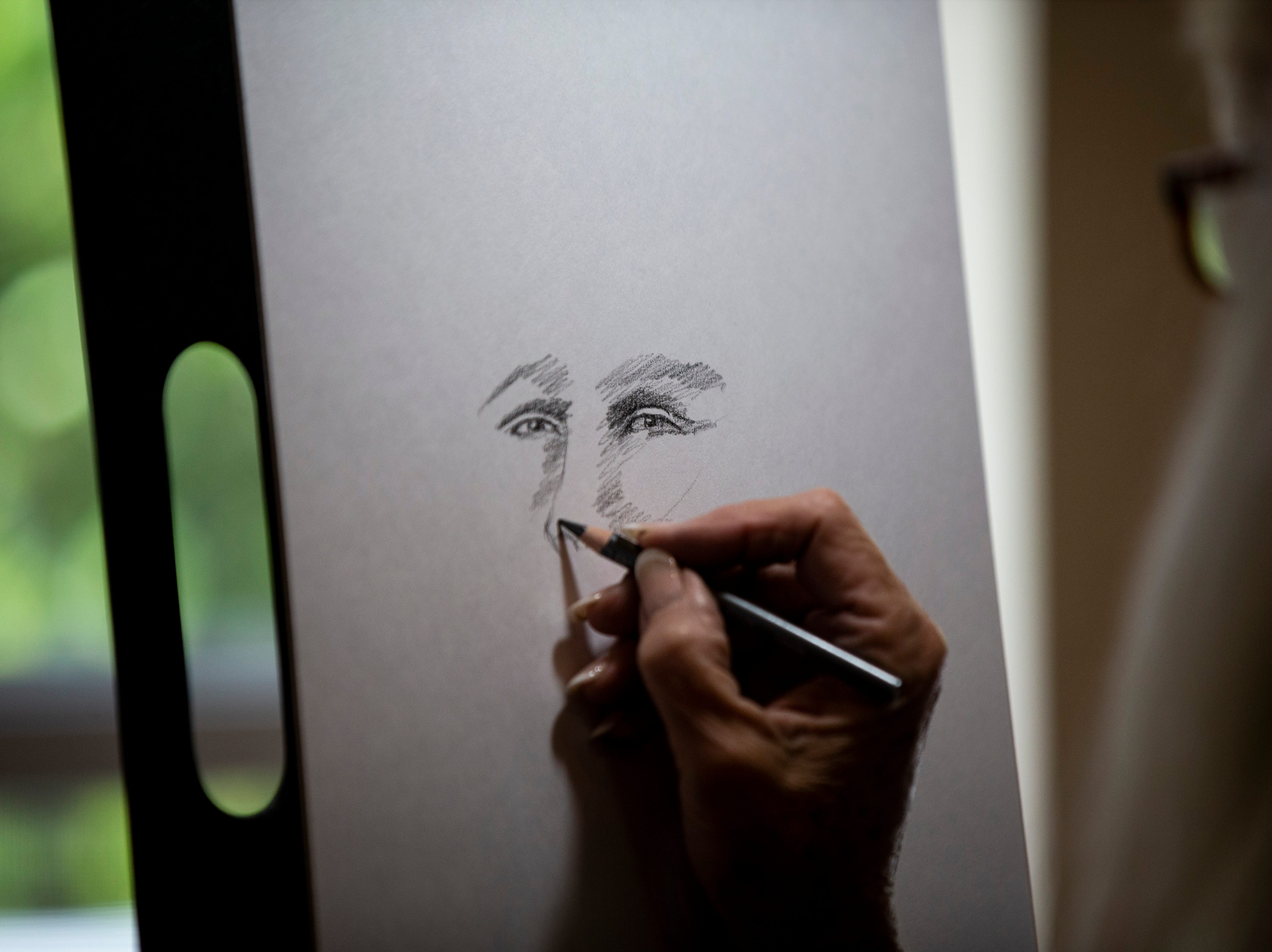 Diane Marshall draws a portrait of Mindi Morrall's spirit guide during the Naples Mystic Faire on Saturday, November 24, 2018, at Études De Ballet & Co in Naples.