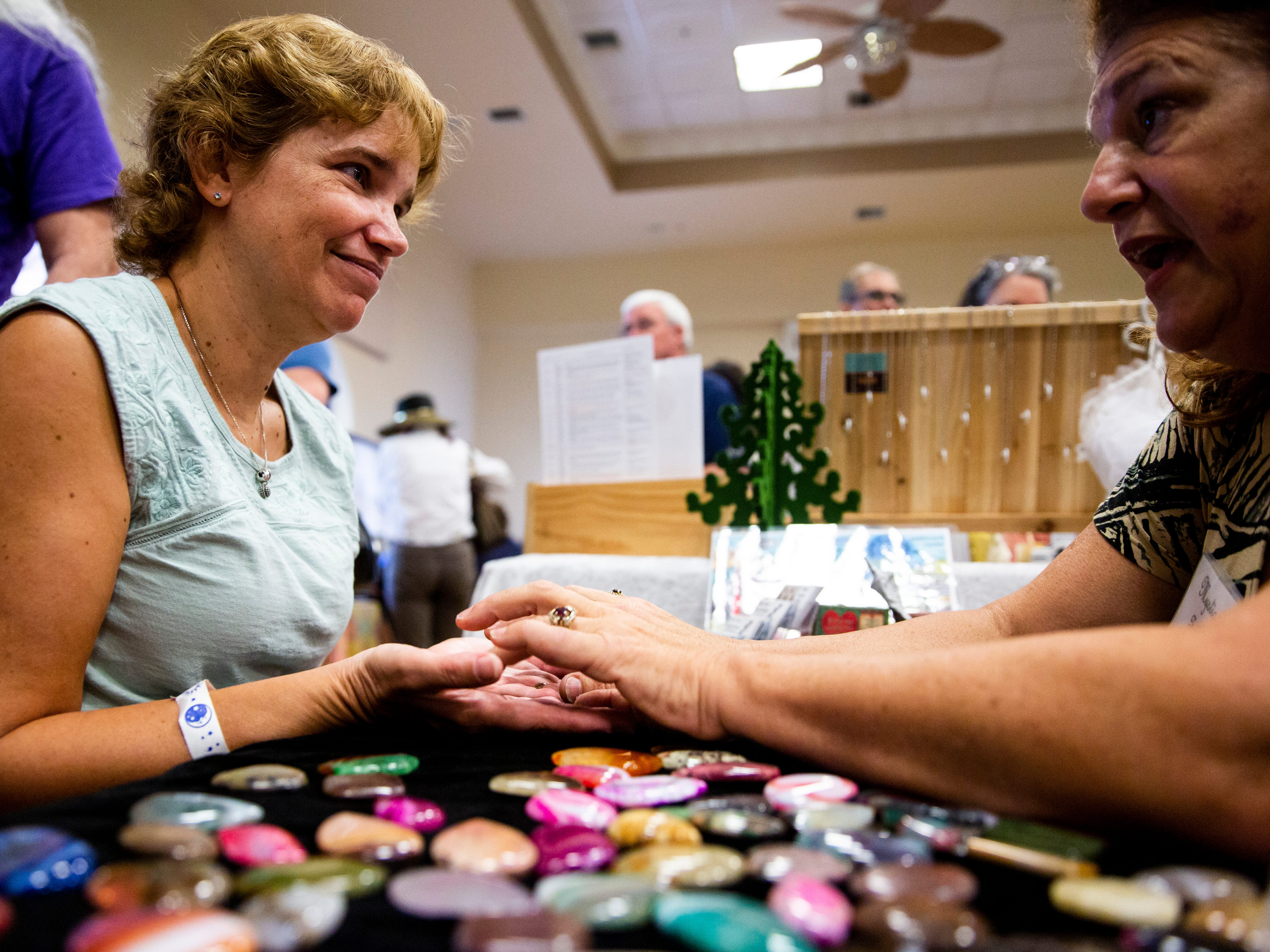 Christine Hall explains to Kimberly Baker the process of picking the right stone for her power shield during the Naples Mystic Faire on Saturday, November 24, 2018, at Études De Ballet & Co in Naples.