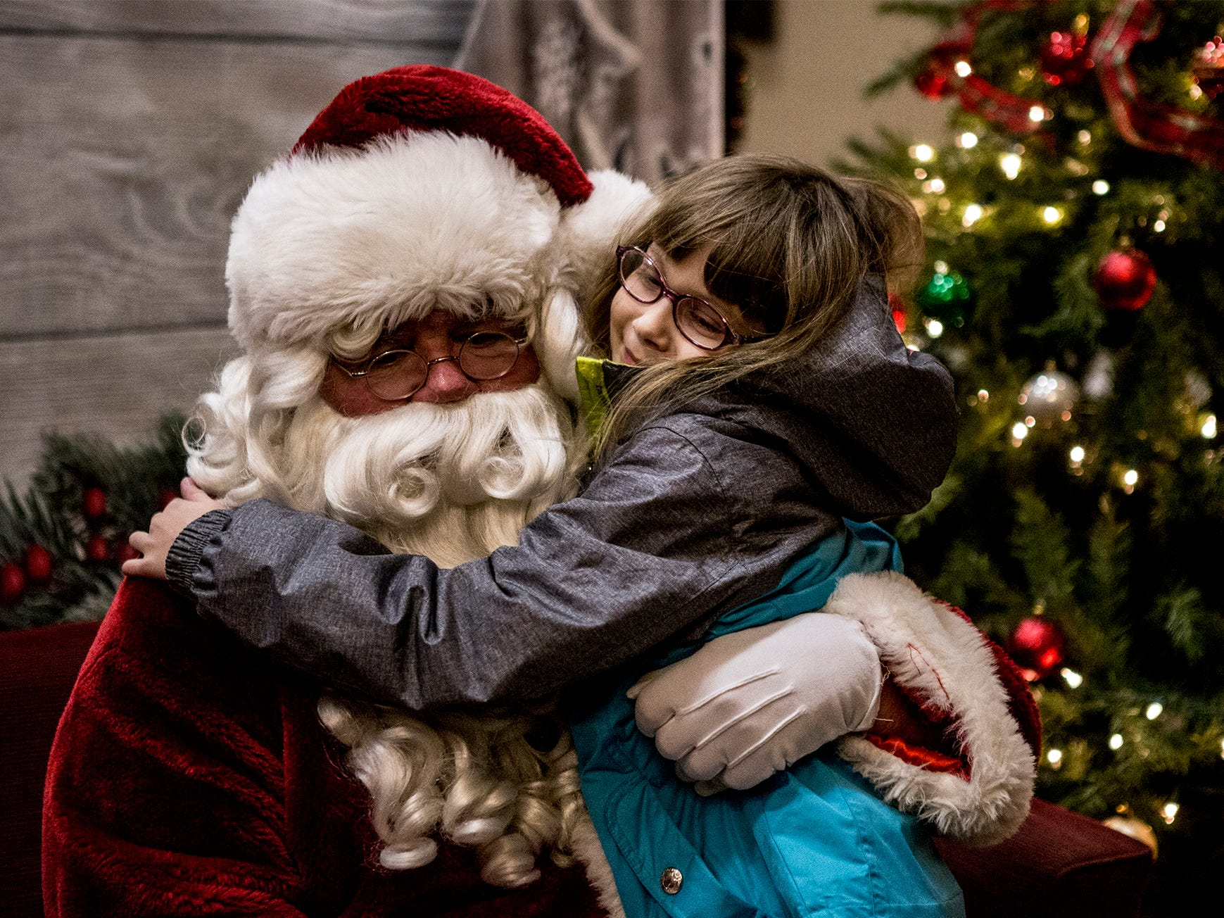 Kaylynn Duncun, 7, hugs Santa after asking him for a remote control Wally robot.