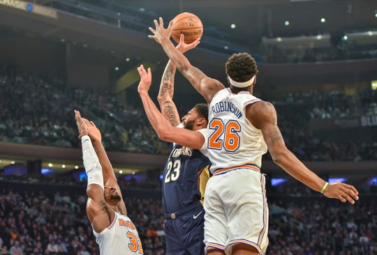 New York Knicks center Mitchell Robinson (26) slaps away a shot-attempt by New Orleans Pelicans forward Anthony Davis (23) in the first quarter of an NBA basketball game, Friday, Nov. 23, 2018, in New York.