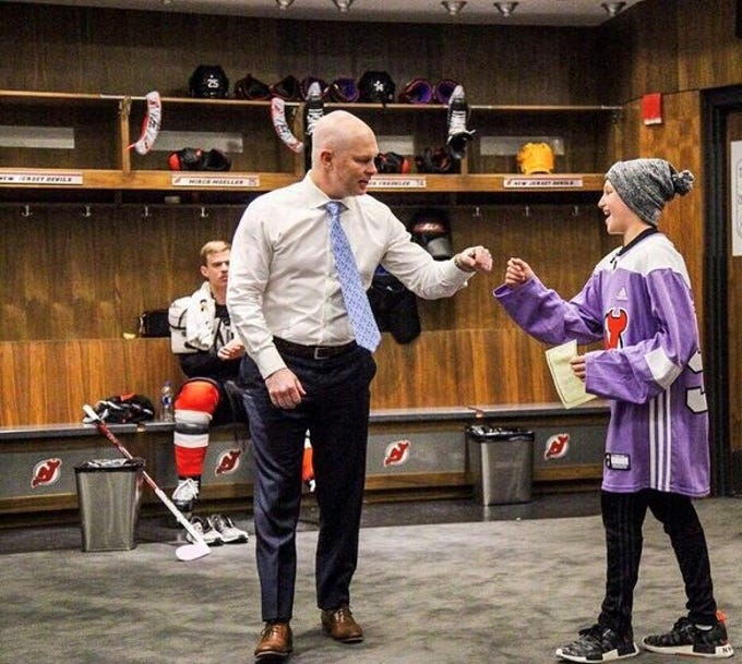 Englewood's Bennett Burgida, an 11-year-old lymphoma survivor and lifelong Devils fan, right, with NJ Devils coach John Hynes in the Devils locker room before the Hockey Fights Cancer game against the Islanders at Prudential Center, Friday, Nov. 23, 2018.