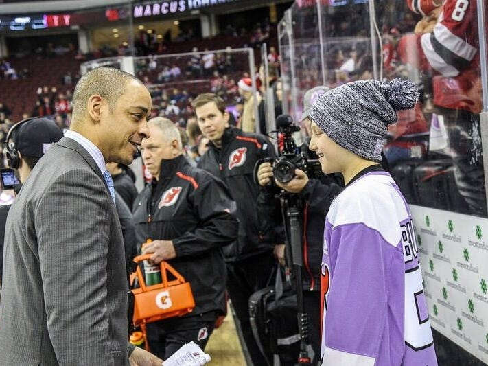 Englewood's Bennett Burgida, an 11-year-old lymphoma survivor and lifelong Devils fan, right, talks with former NJ Devils player and current Devils analyst Bryce Salvador before the Hockey Fights Cancer game against the Islanders at Prudential Center, Friday, Nov. 23, 2018.